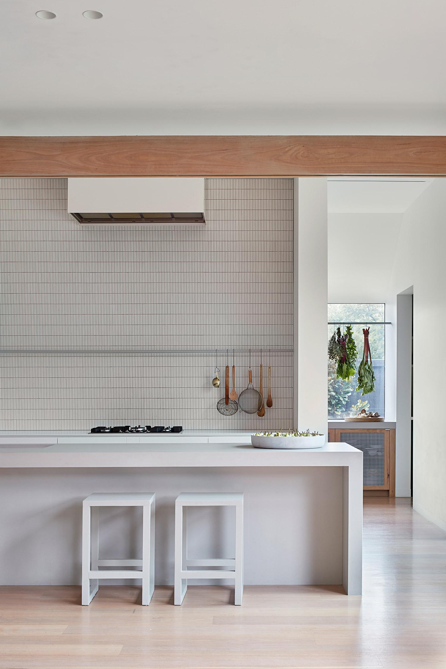 A minimalist kitchen with an island and tiled wall.
