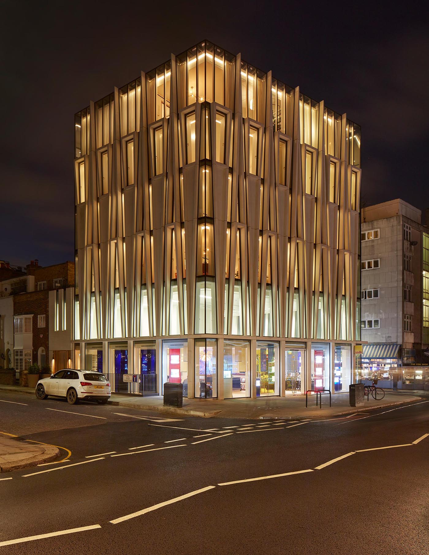 A modern mixed-use building with a facade inspired by candle-making.