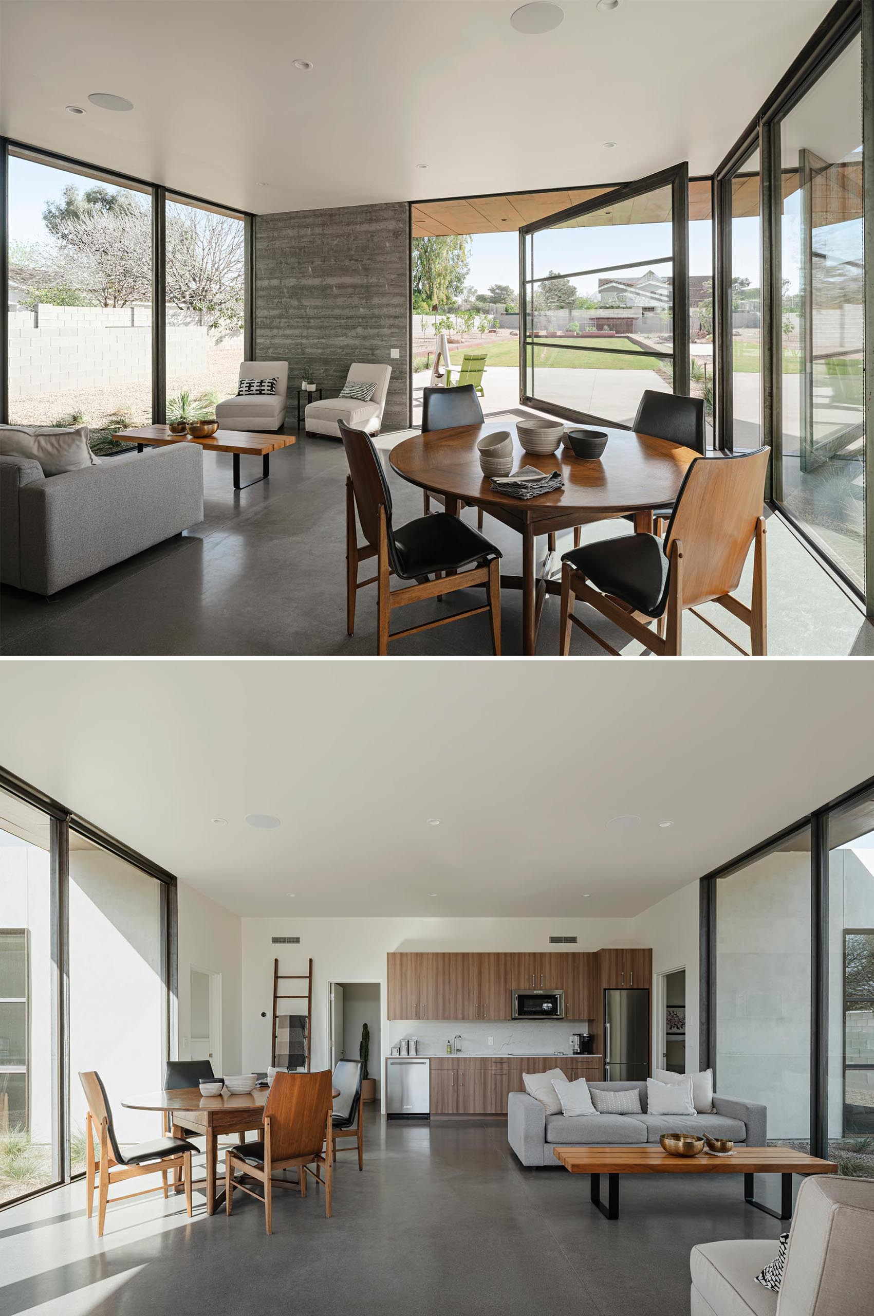 An open plan living room, dining area, and kitchen, with polished concrete floors and a large pivoting door.