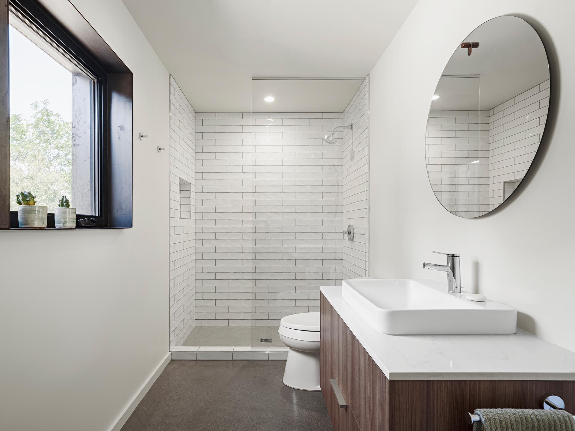 A modern white bathroom with a wood vanity and white rectangular tiles.