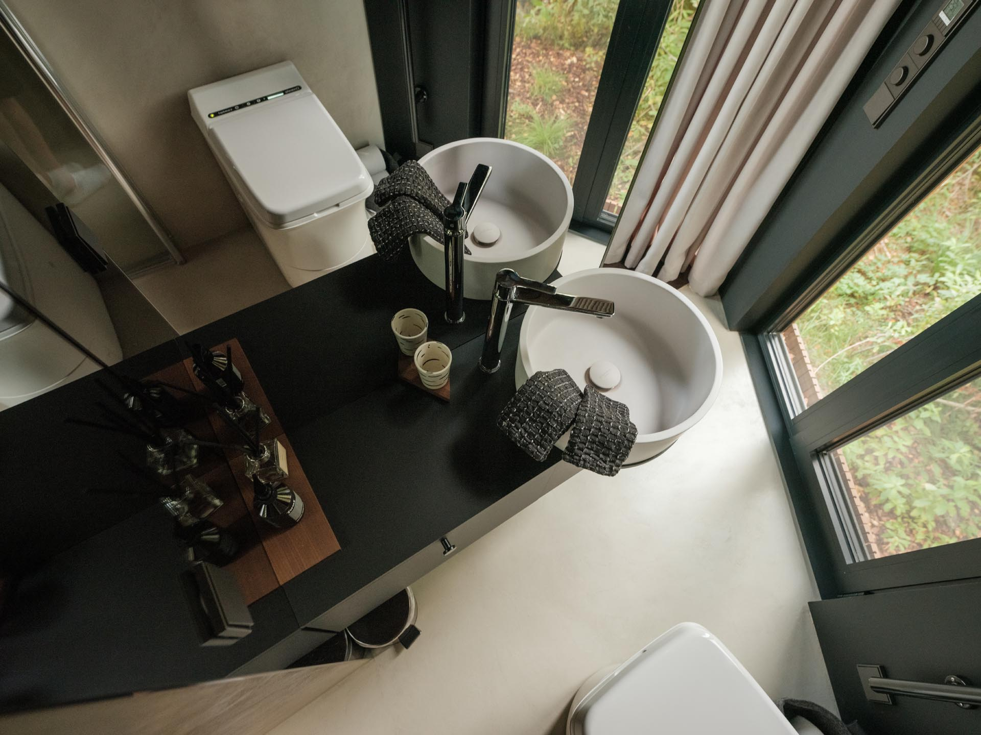 A small bathroom that includes floor-to-ceiling mirrors and an incineration toilet.