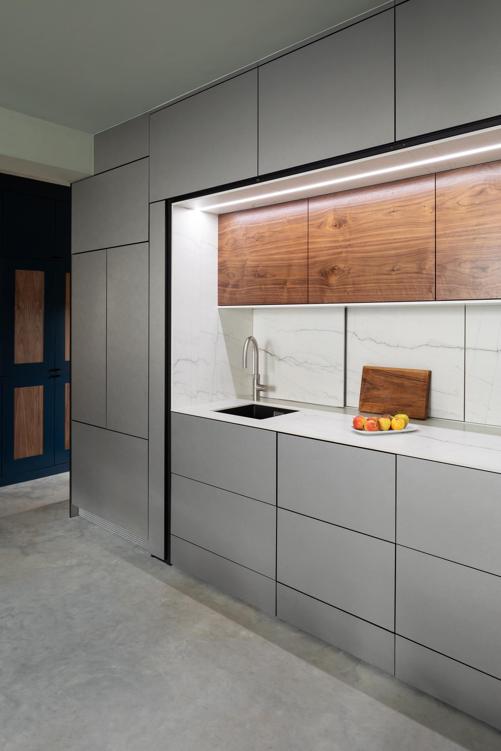 The main section of this modern kitchen includes a small sink, a cooktop, counter space, hidden lighting, drawers with minimalist fronts, and wood upper cabinets.