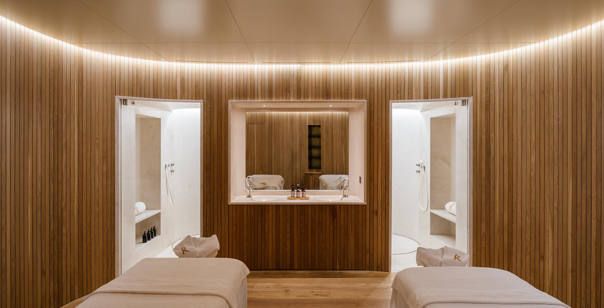 Modern massage rooms with wood slat curved walls and hidden lighting.