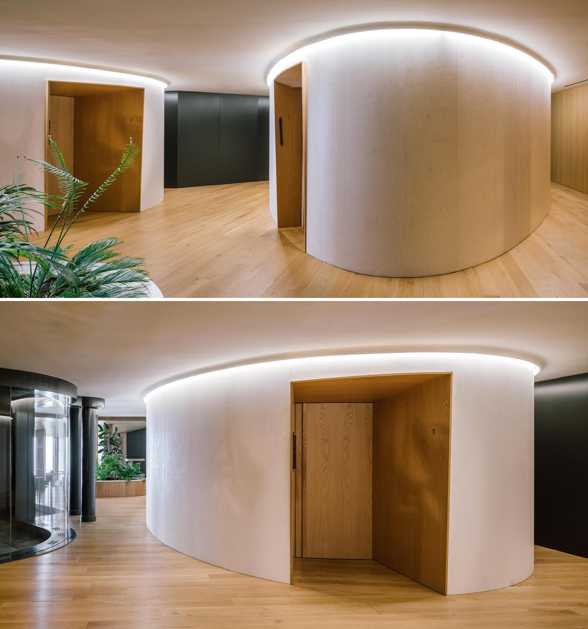 Inside a modern hotel spa, light wood walls are accented by recessed doors, while hidden lighting creates a glow that highlights the curved walls.