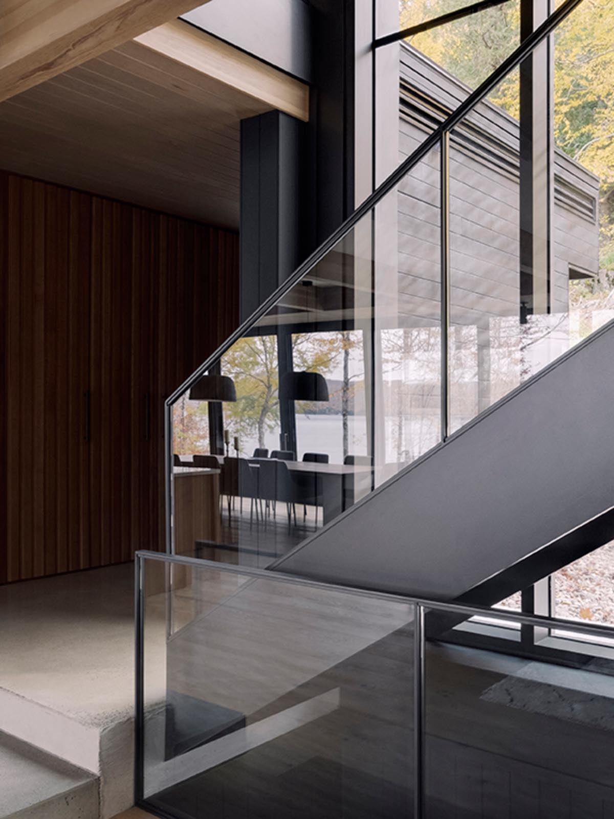 Steel and glass stairs connect the various levels of the home, with the adjacent windows providing ample natural light.