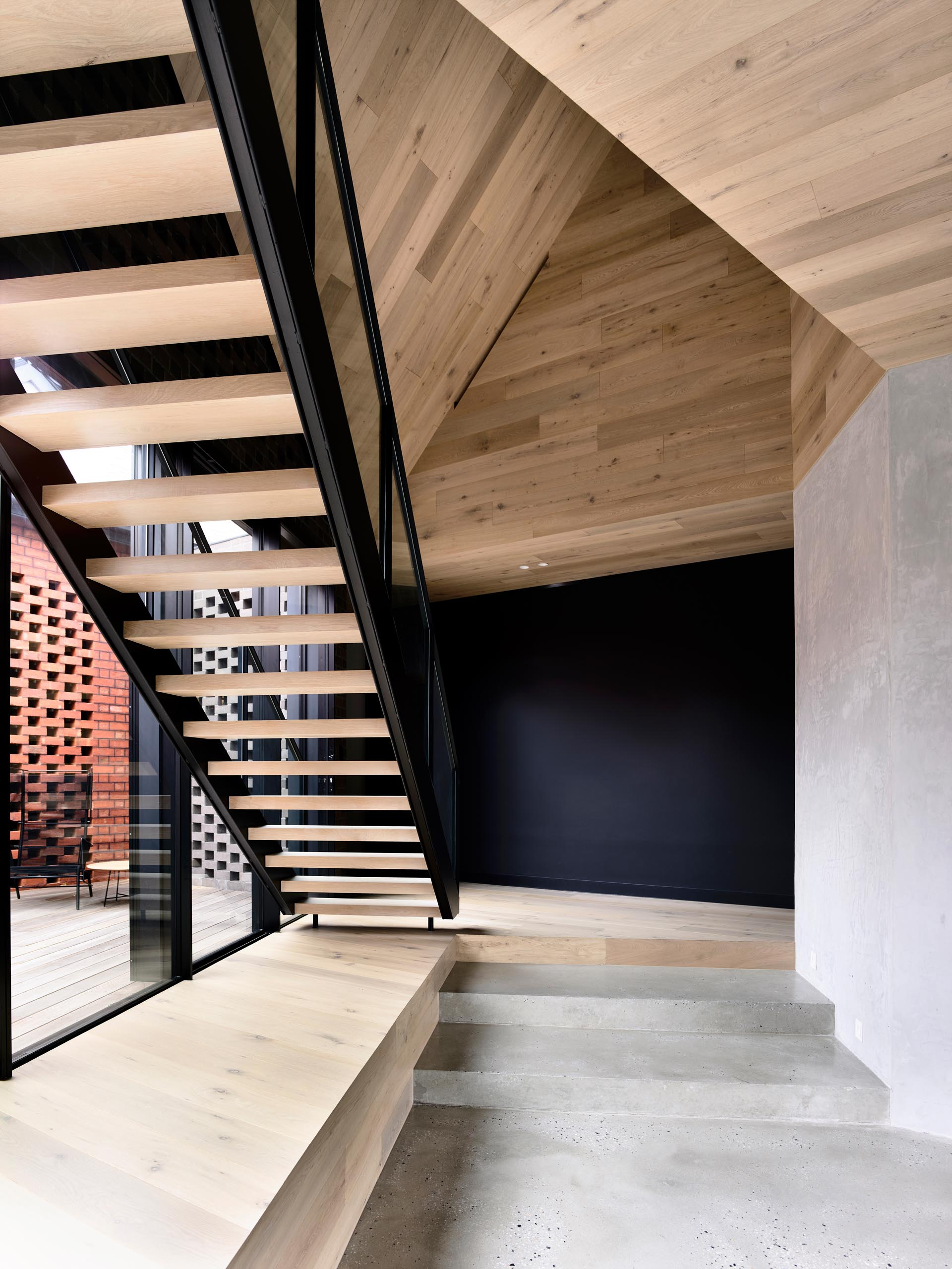 A modern sculptural wood, steel, and glass staircase which is set under a folding origami, timber-lined ceiling.