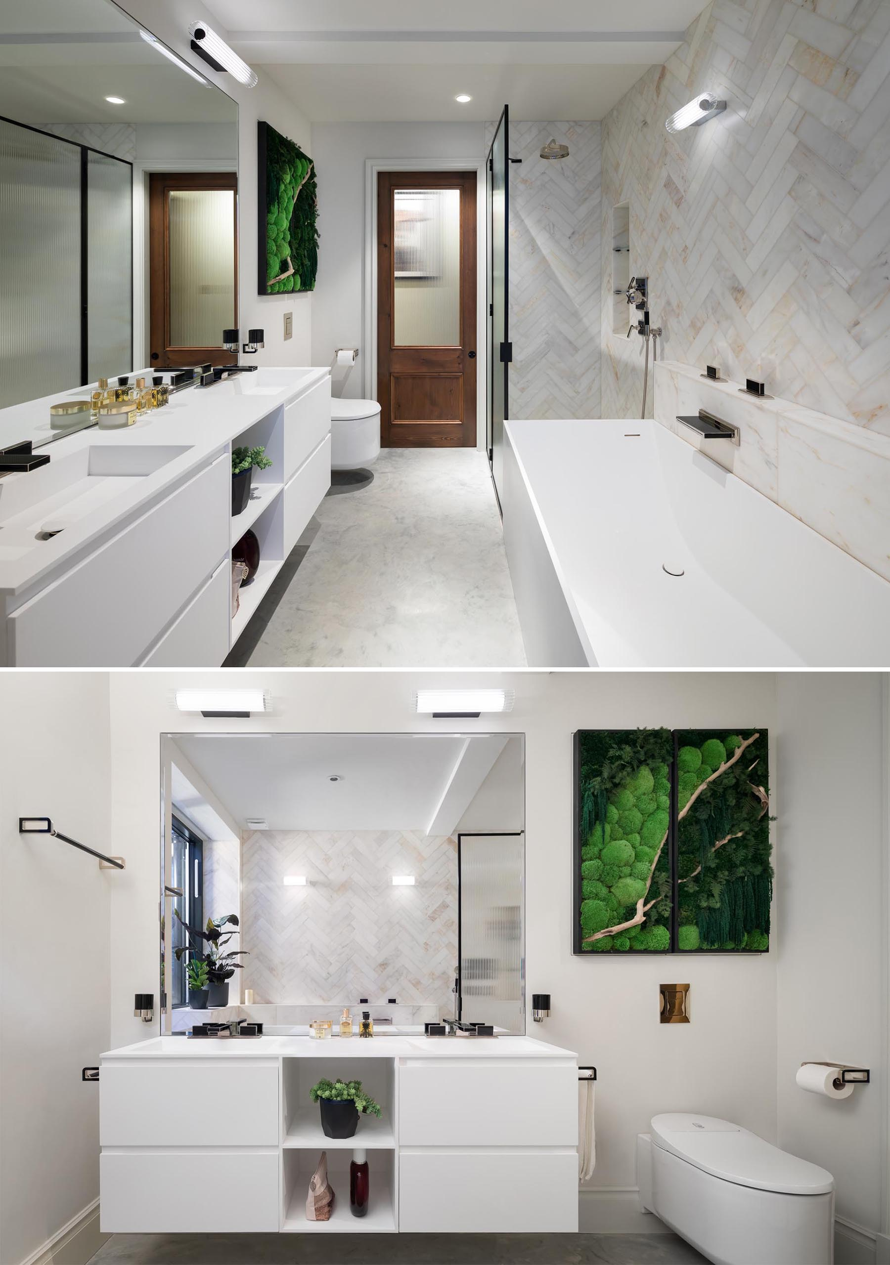 In this modern bathroom, there's a white vanity with dual sinks, a matching bathtub, as well as a walk-in shower and a storage cabinet that hangs above the bathroom and adds a natural design element.