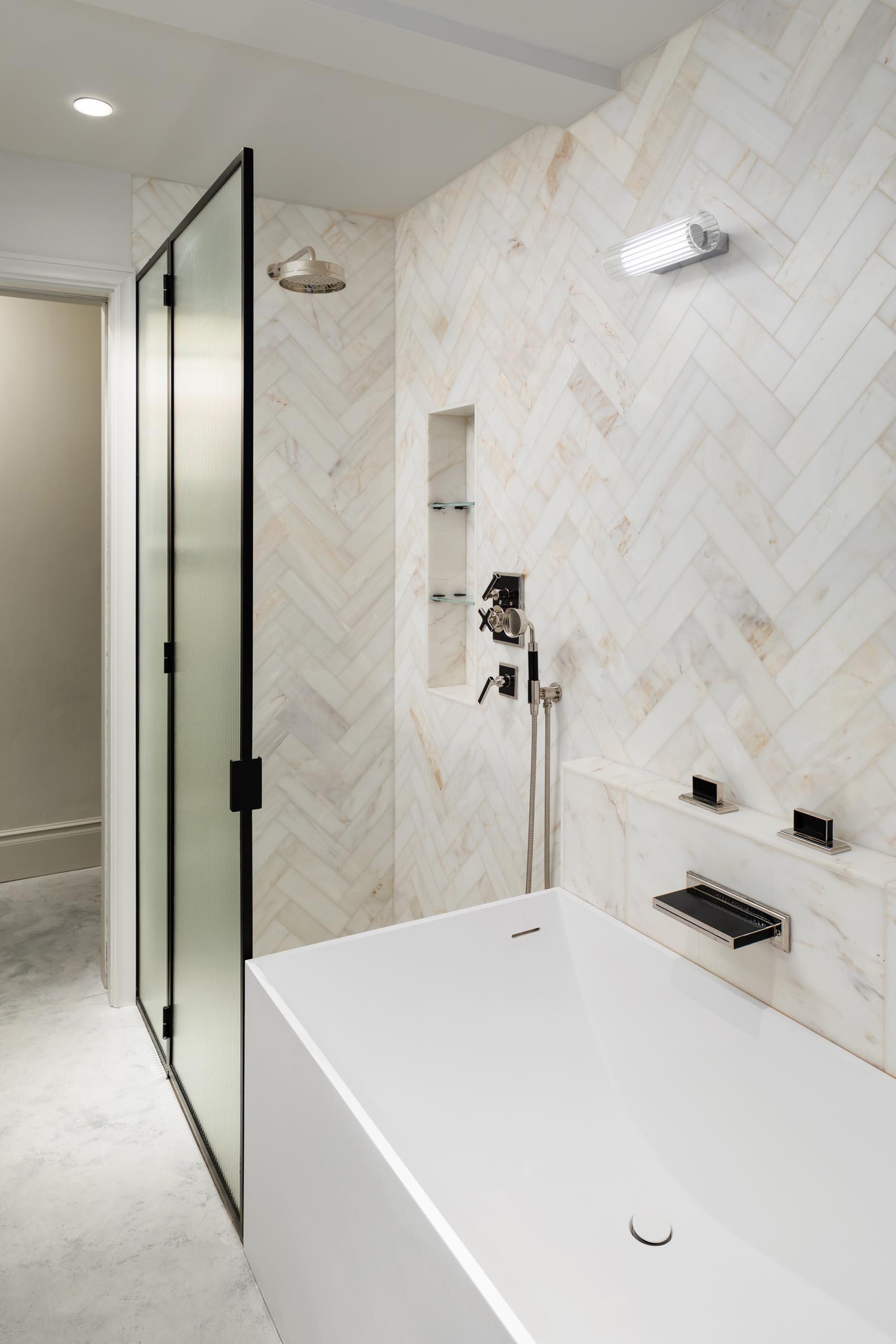 A modern bathroom with a walk-in shower that meets the bathtub.