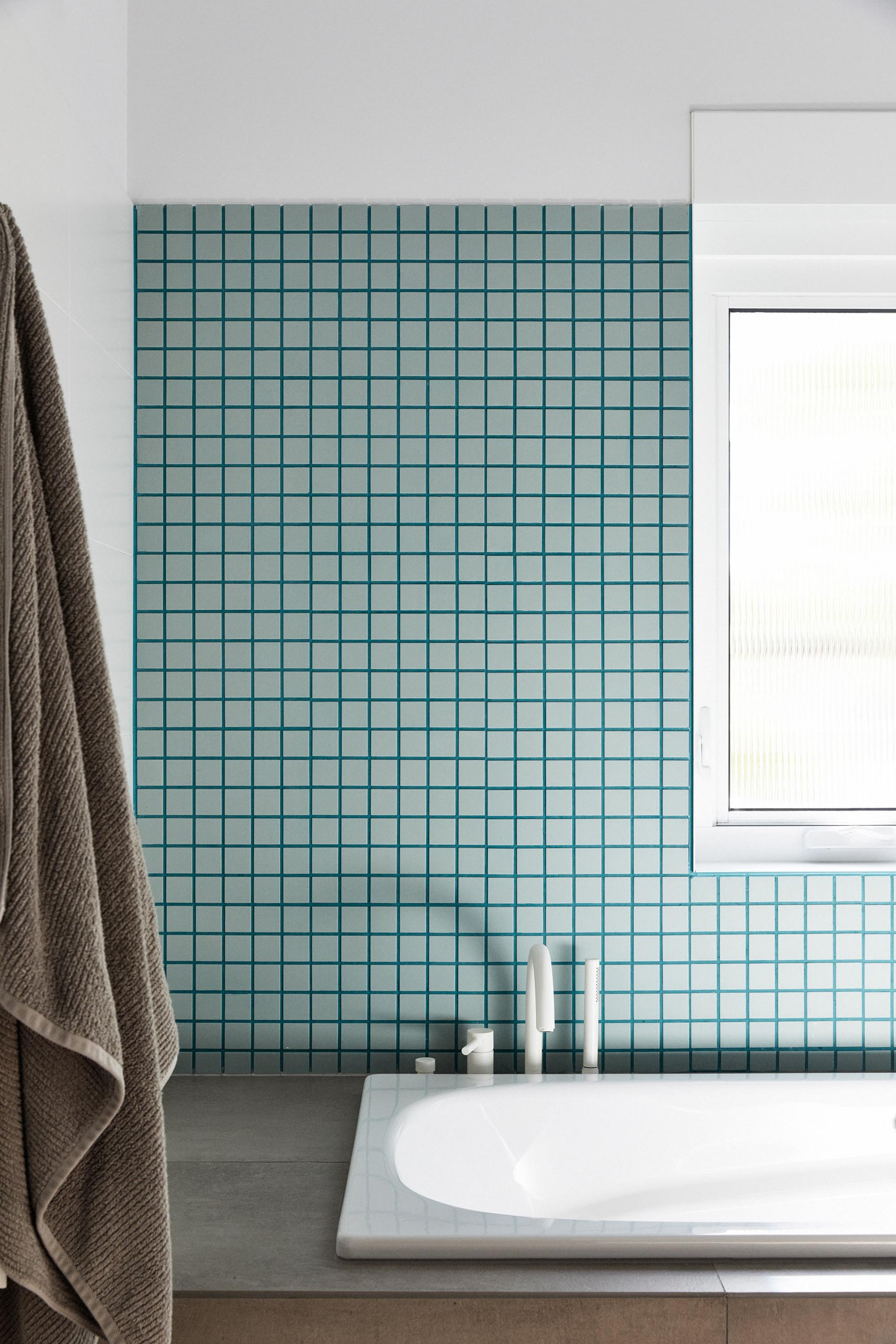 In this modern bathroom, white walls have been paired with soft blue/green tiles and matching grout for a contemporary look.