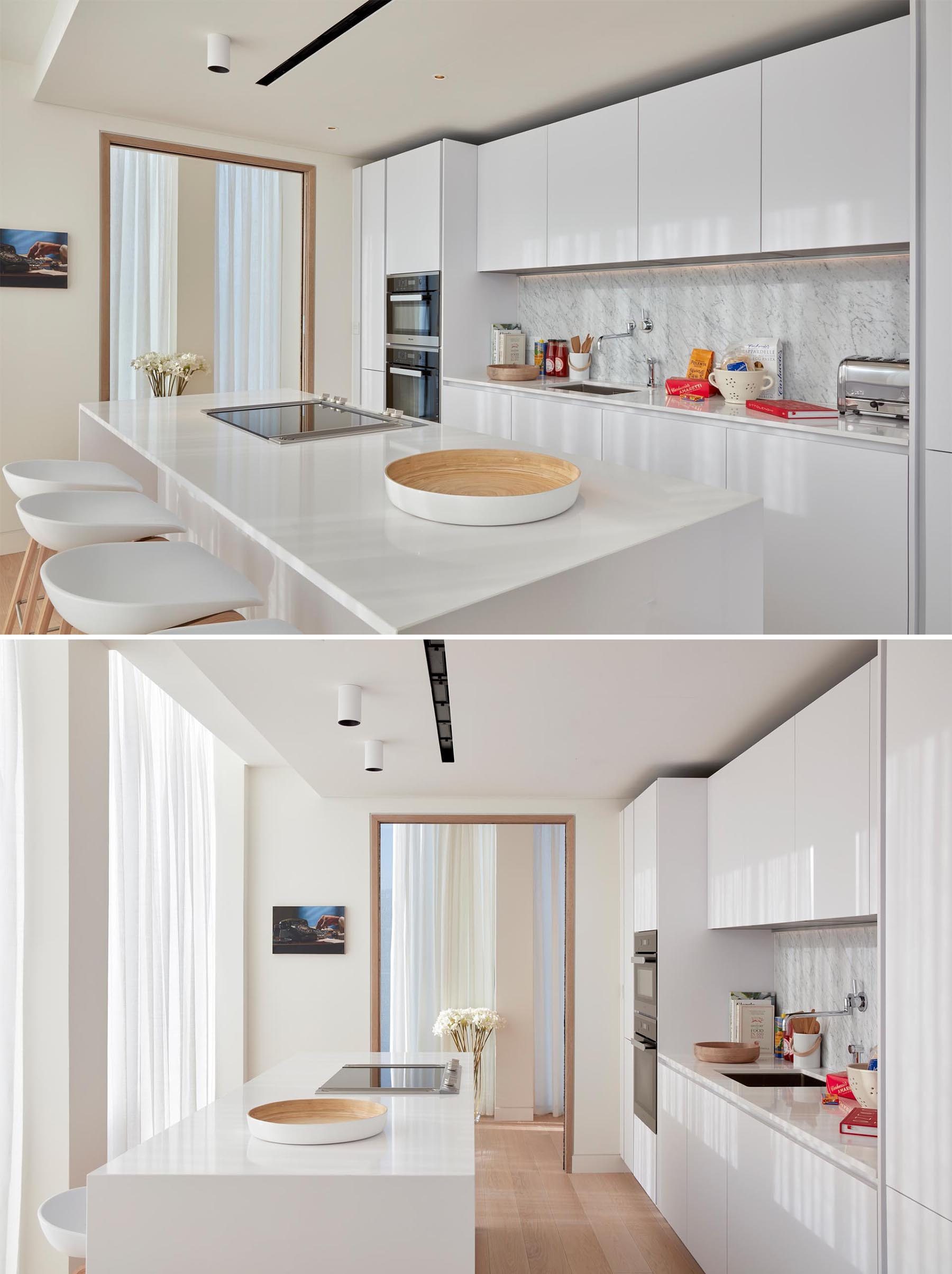 In this modern kitchen, minimalist white cabinets have been used to complement the white countertop and light backsplash.