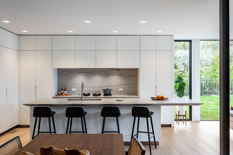 A modern kitchen designed with floor-to-ceiling minimalist white cabinets, and an island with a cantilevered countertop.