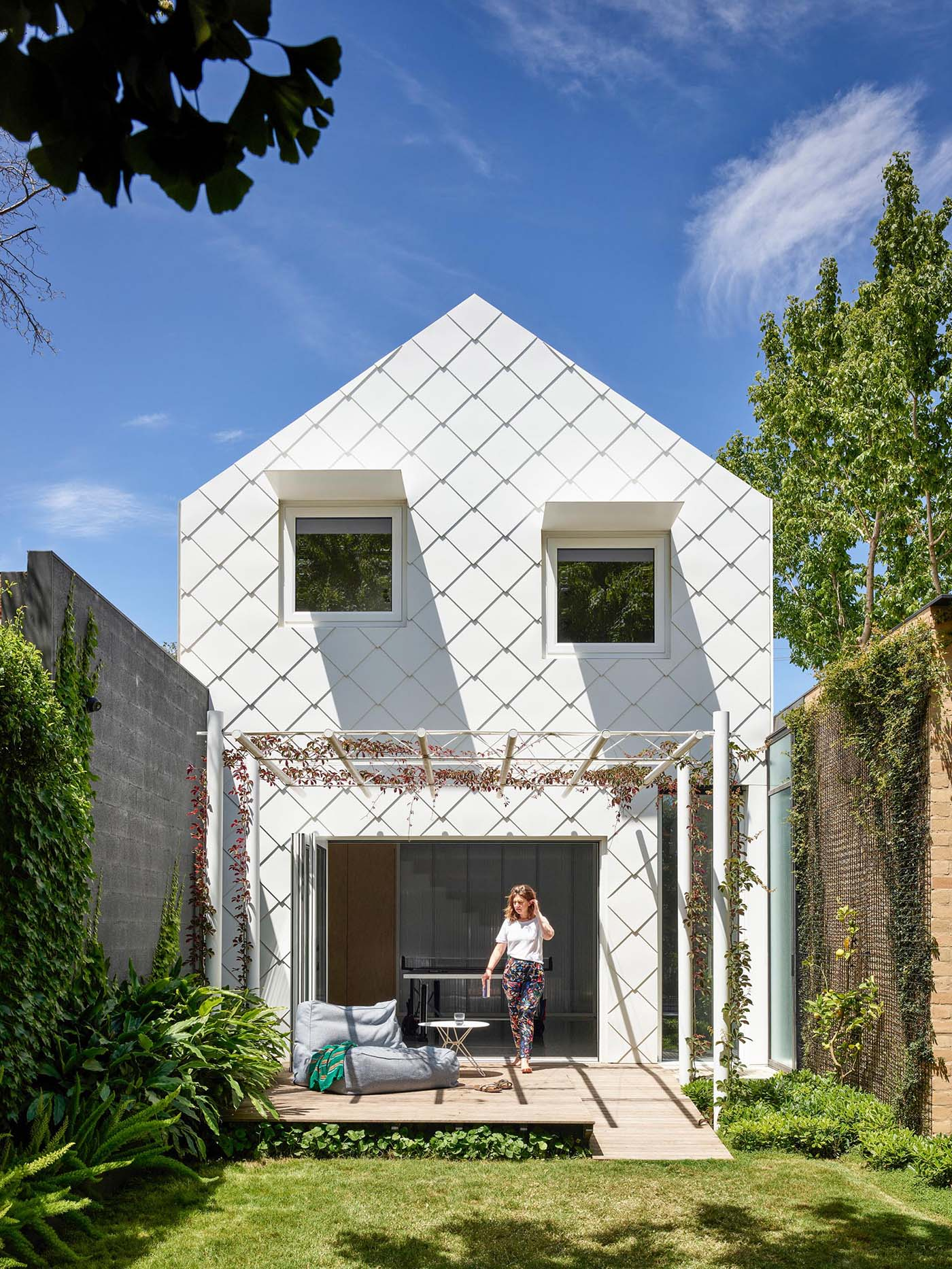 The exterior of this modern home looks like a pretty, white shingled cottage with a perfect pitched roof.