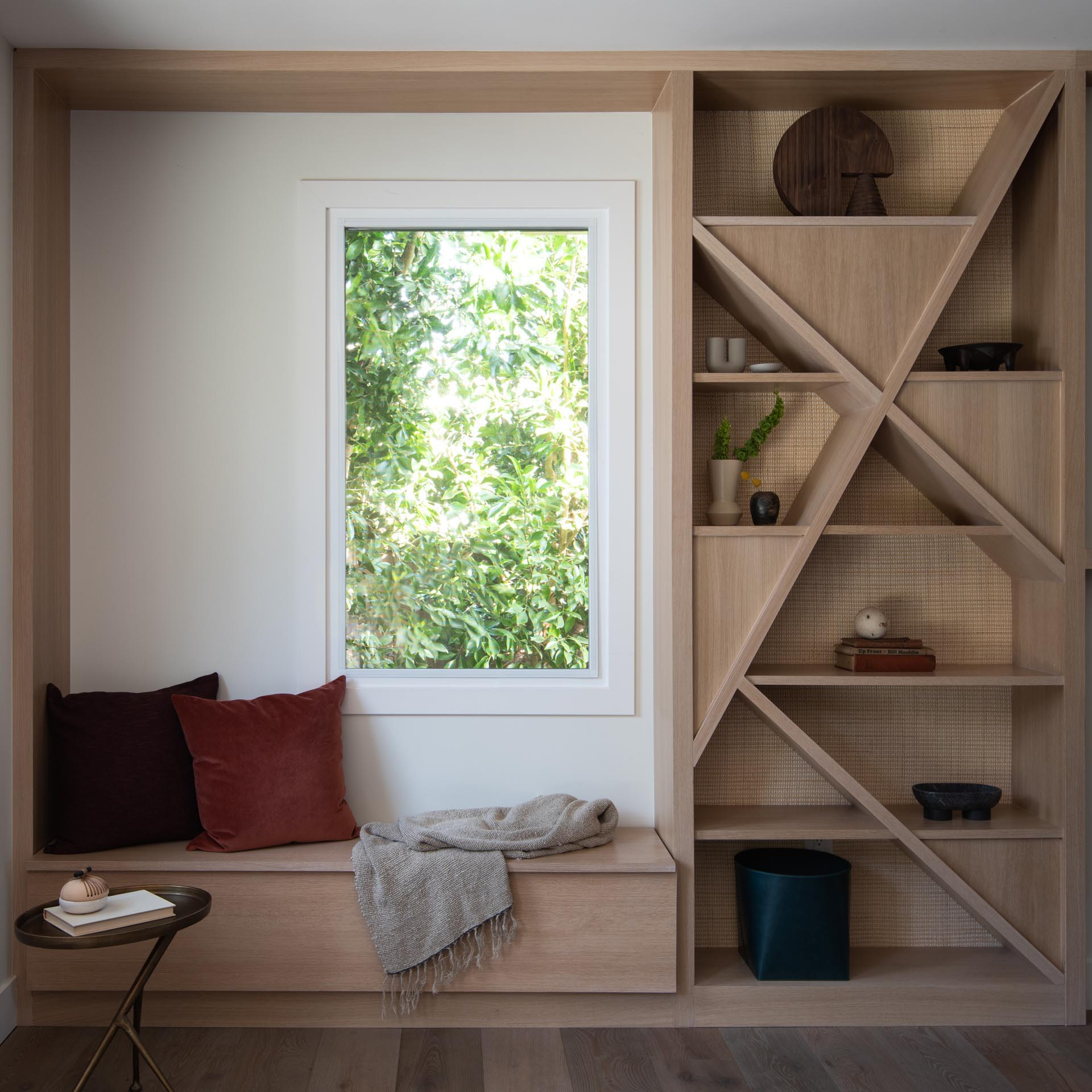 A modern shelving unit with a natural cane backing has been installed next to a window seat.
