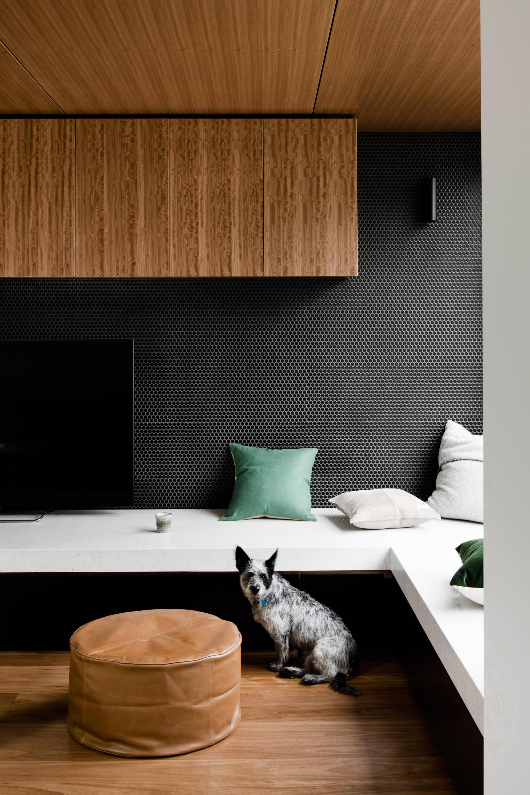 A modern built-in tv stand with a black penny tile backdrop, transforms into a daybed by a window.