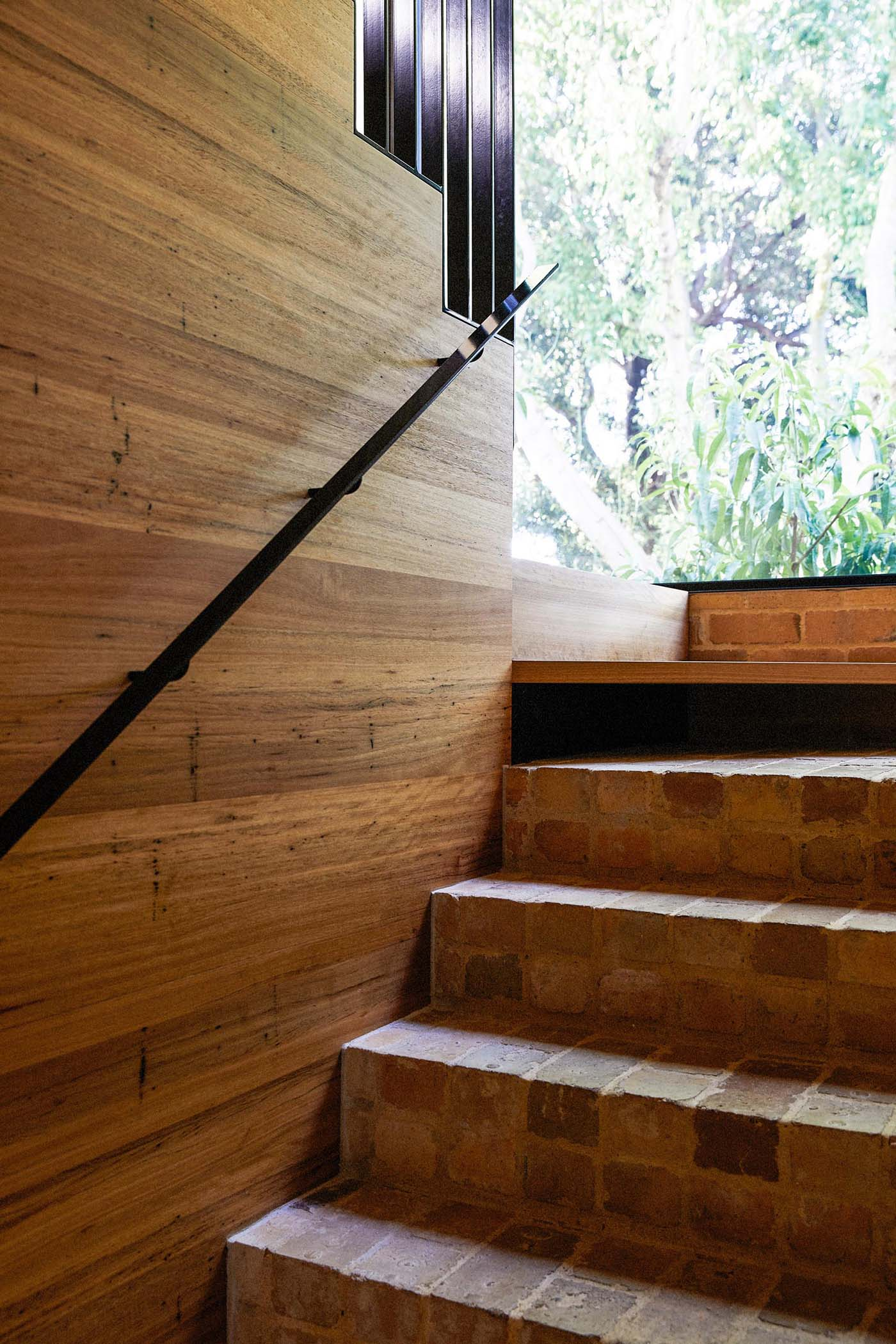 This staircase features the recycled yellow bricks that then transition to connect with the wood stair treads. A large black framed window perfectly frames the tree and outdoor dining area.