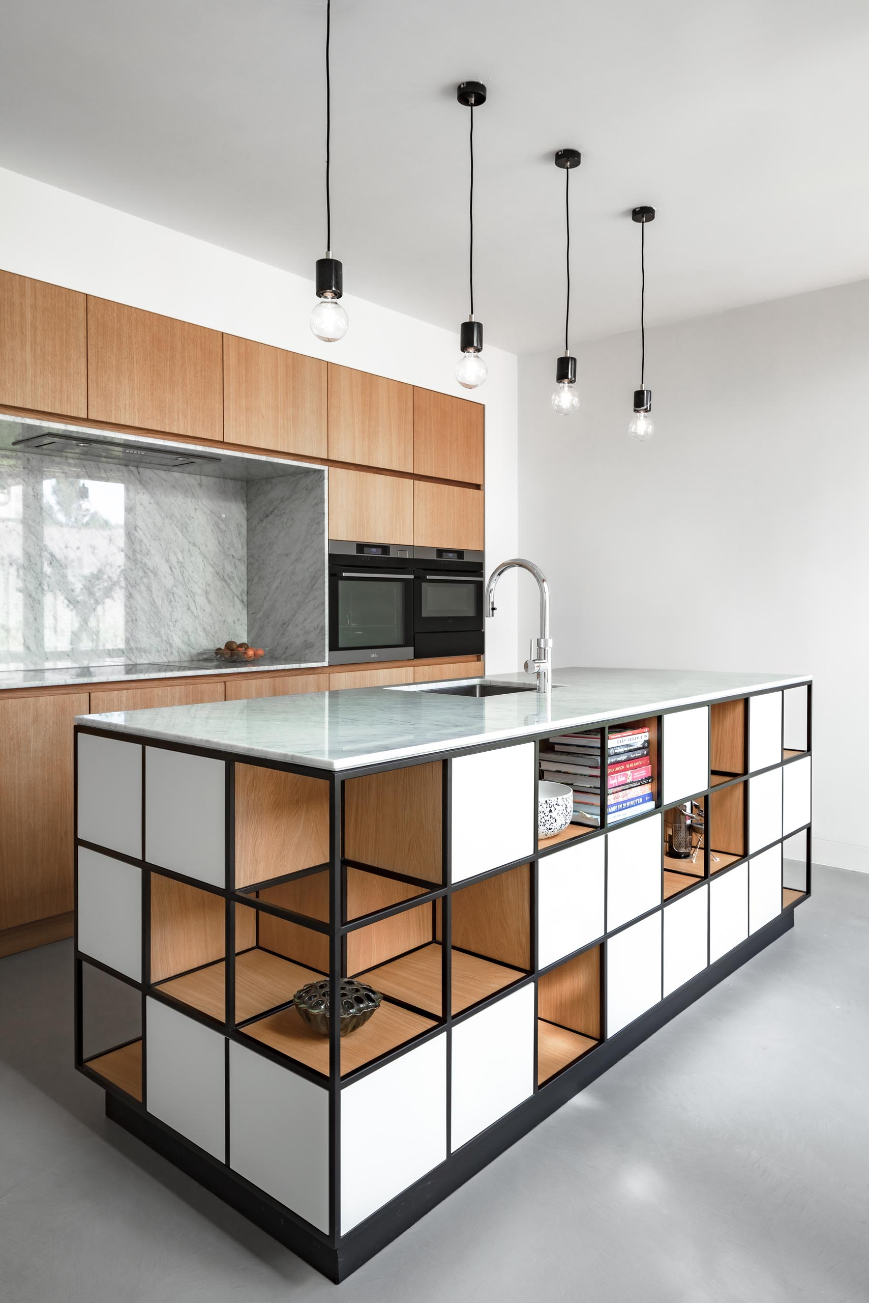 In this modern kitchen, hardware-free wood cabinets line the wall, and an island includes a cube like design with shelving.