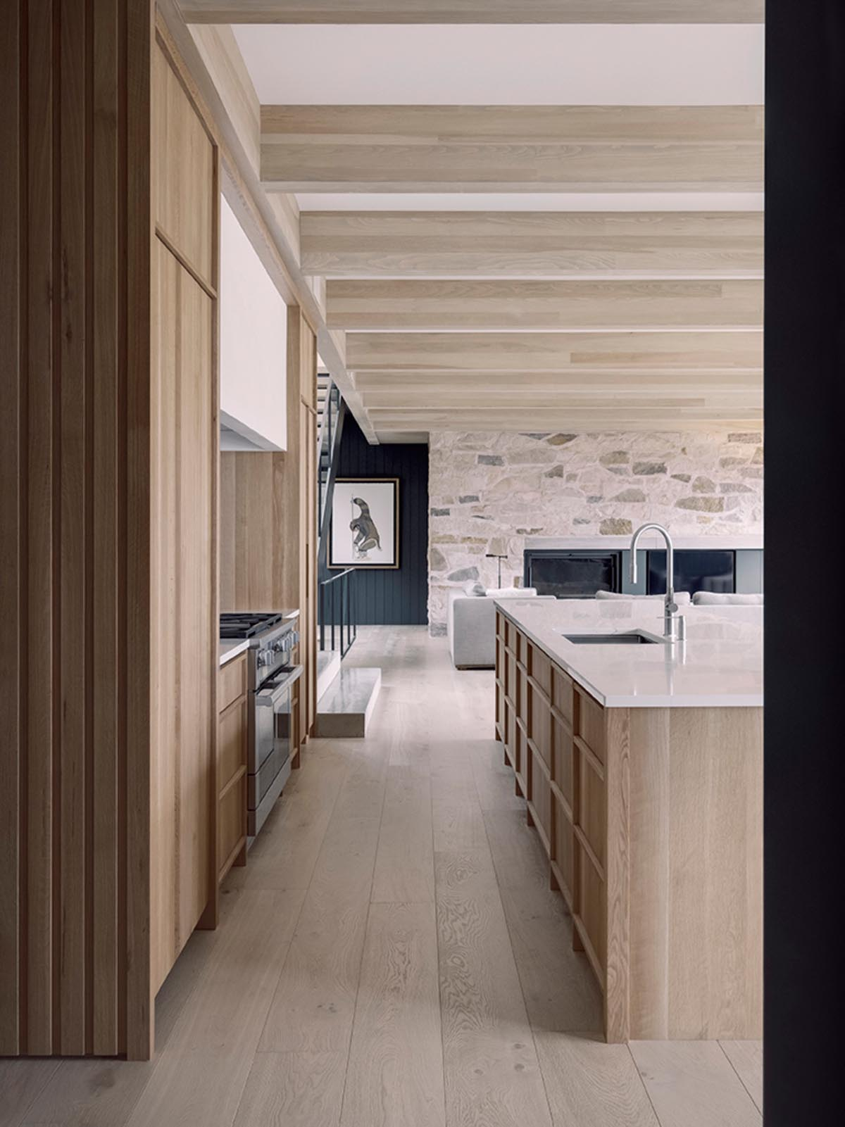A modern kitchen with hardware-free wood cabinets and a large island that increases the available countertop space.