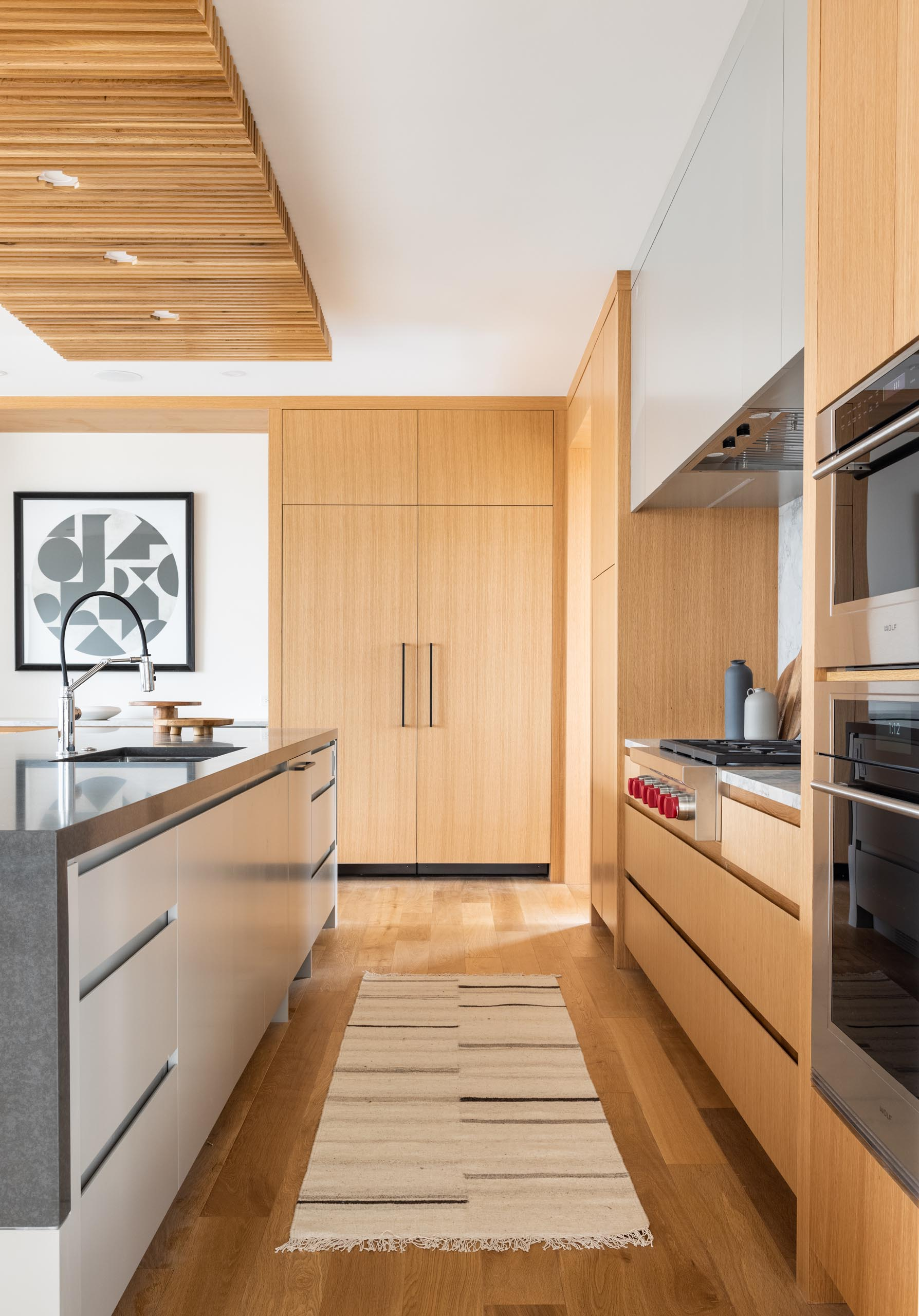 This modern kitchen includes a large island with a wood ceiling accent and light wood cabinets.