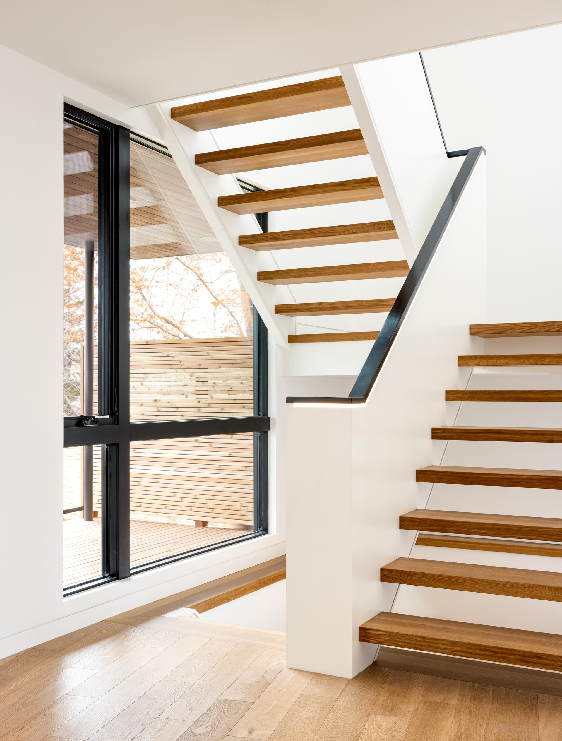 A staircase with wood treads and a black handrail with hidden LED lighting connects to the upper floor of the home.