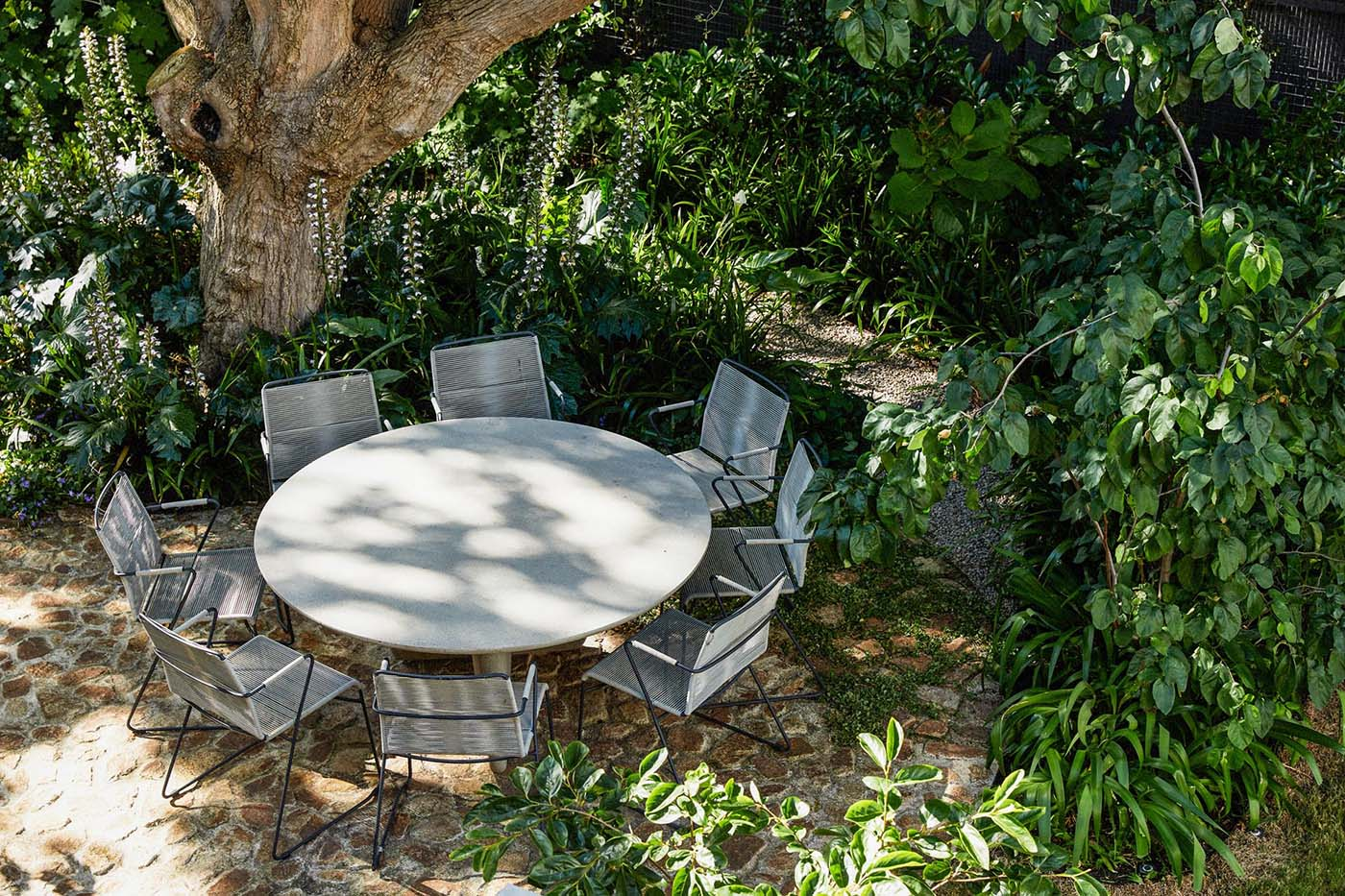 A garden with a round table and stone patio.