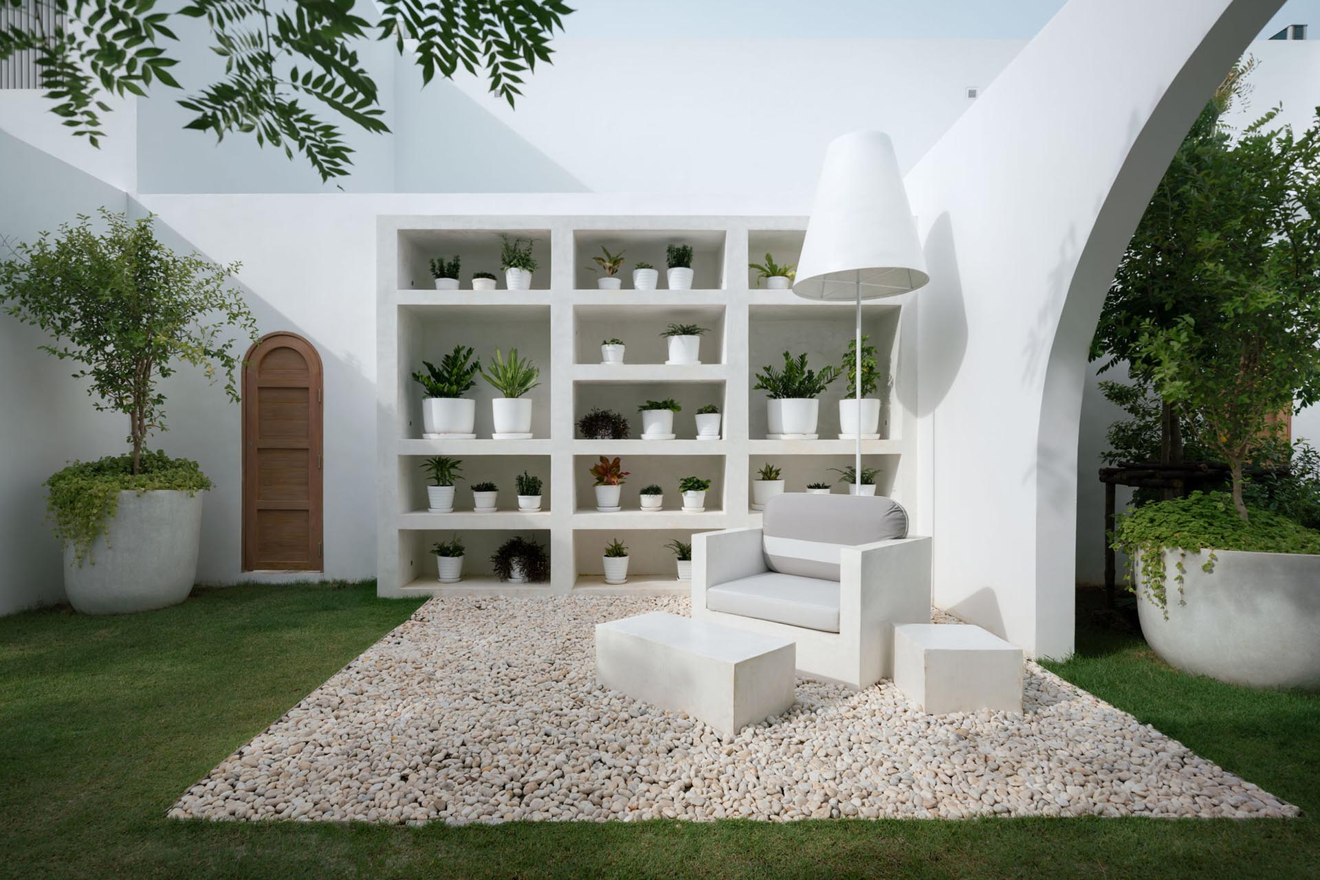 An outdoor living room with a shelving unit designed to house plants.