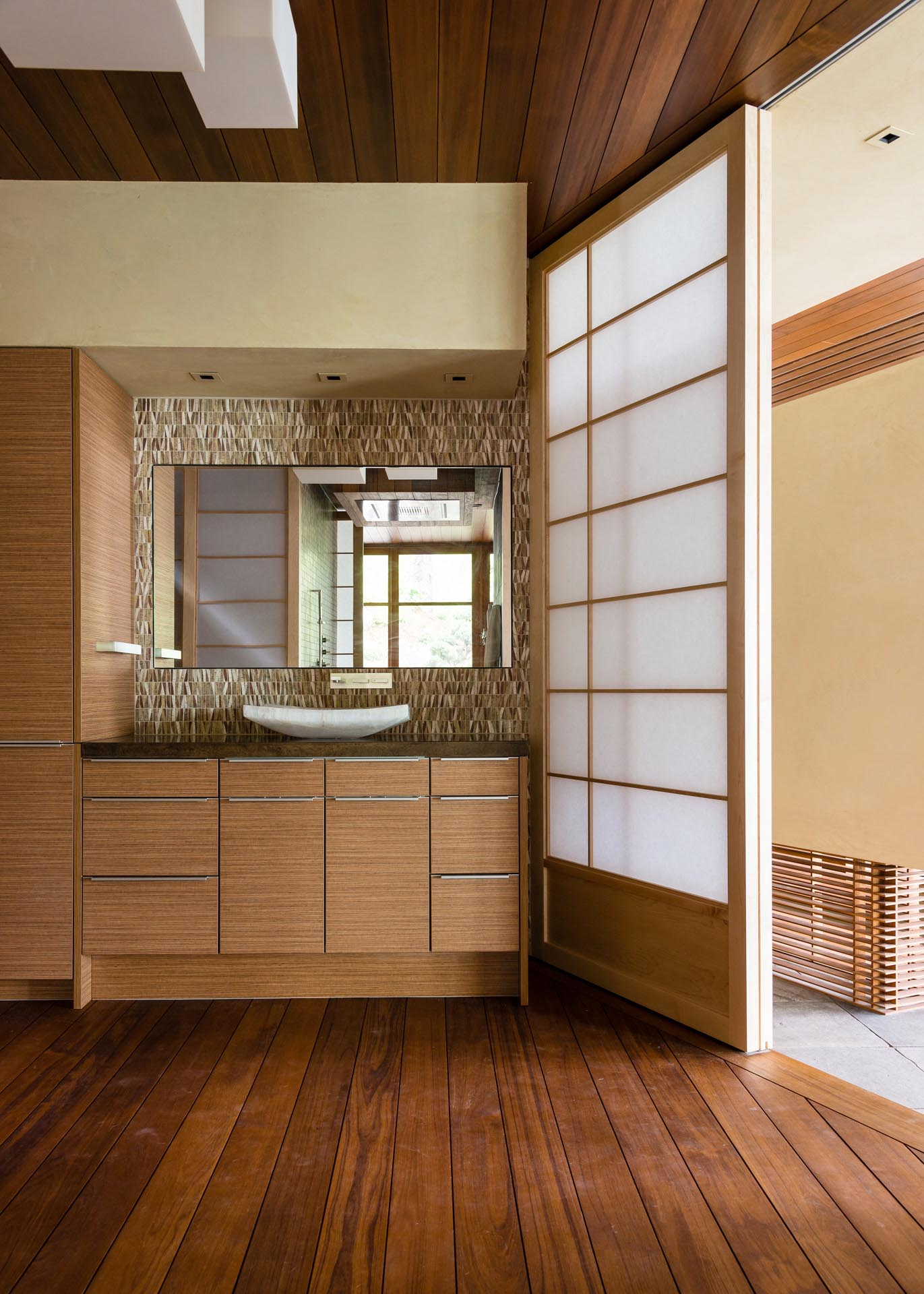 In this bathroom, decorative natural with earthy colors provides a backdrop for the mirror, while a sliding screen door lets the light from the nearby window travel through to the interior space.
