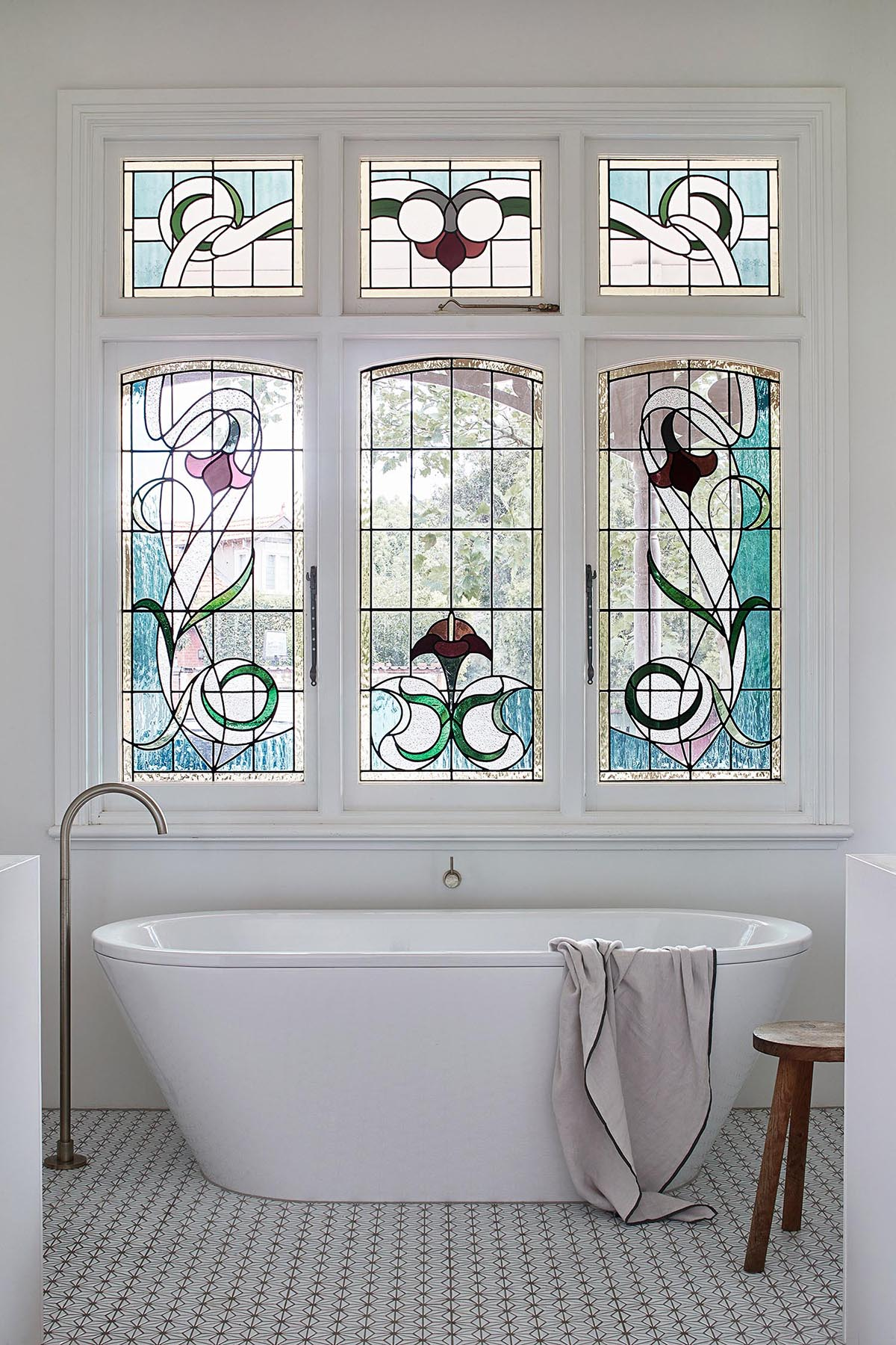 A bathroom with a stained glass window and a modern freestanding bathtub.
