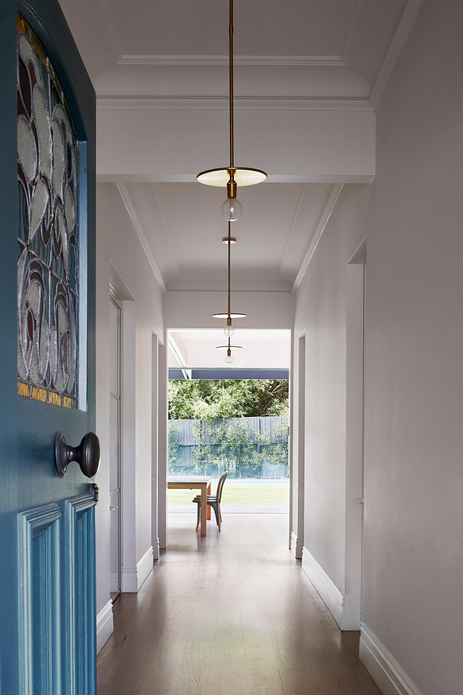 A remodeled house with minimalist lighting in the entry hallway.