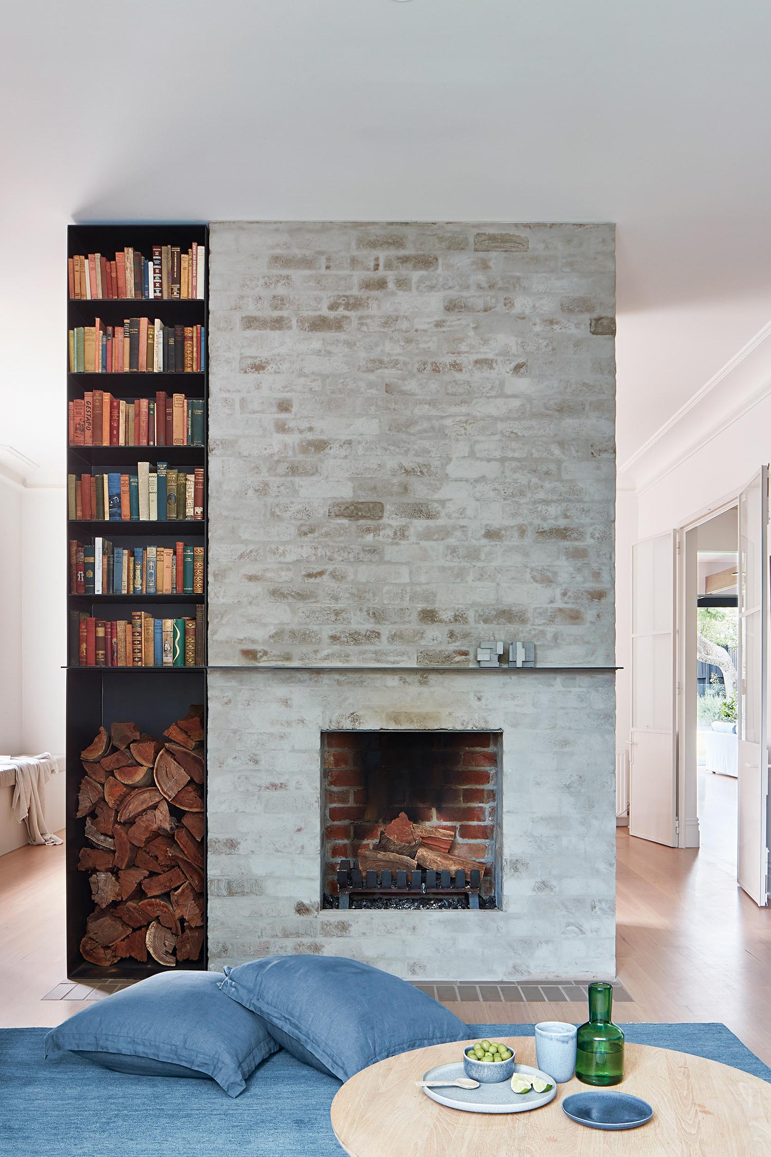 A brick fireplace with firewood storage and a bookshelf.