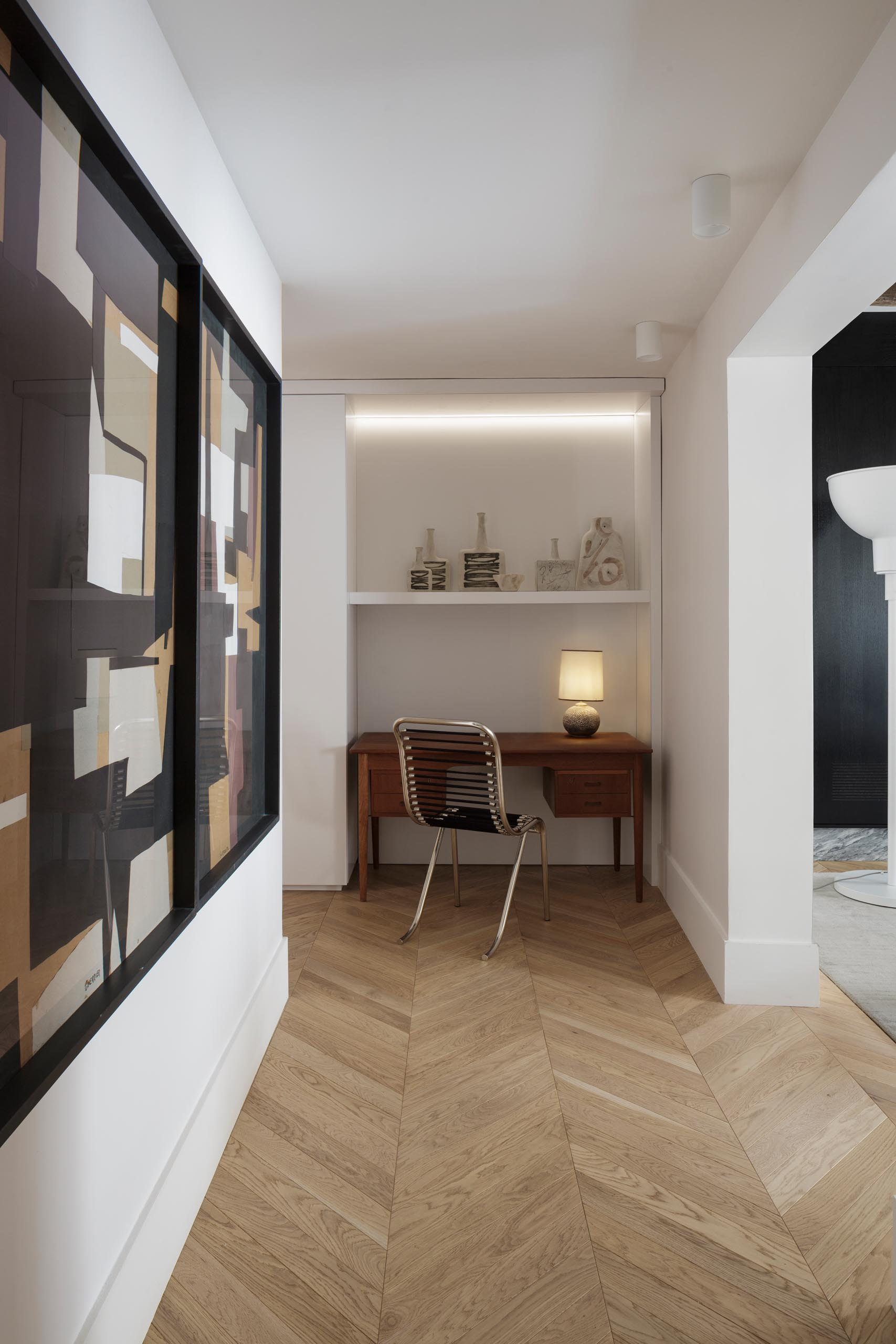 A small home office is located at the end of a hallway, and includes a small wood desk as well as a built-in shelf and hidden lighting.