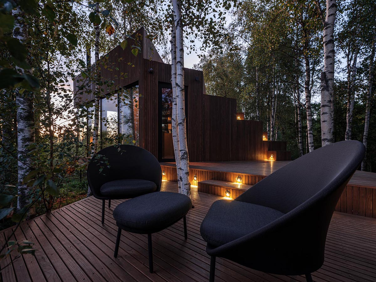 At night, exterior lighting creates a cozy atmosphere for this cabin's deck.