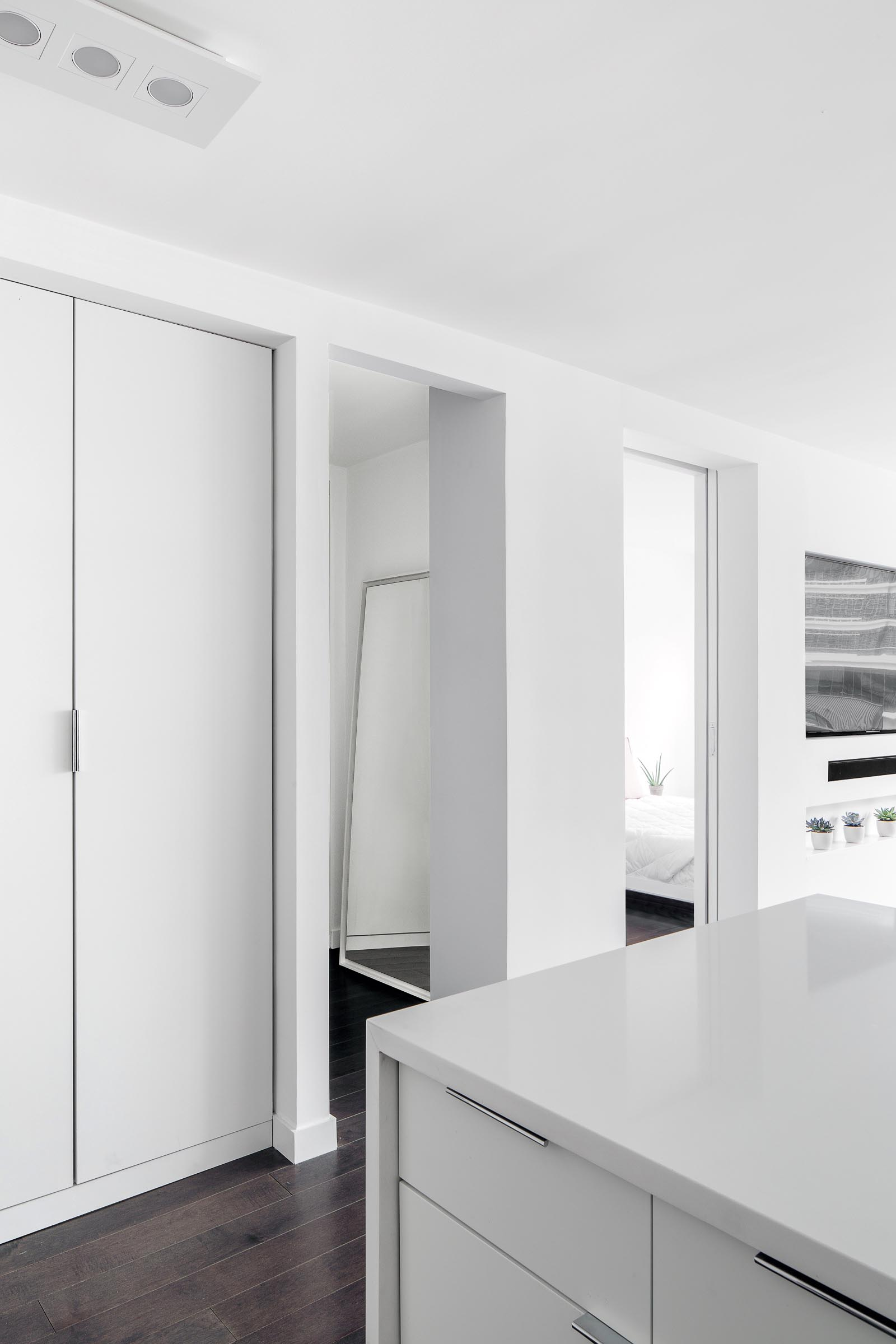 A small apartment with a white interior and dark wood floors.