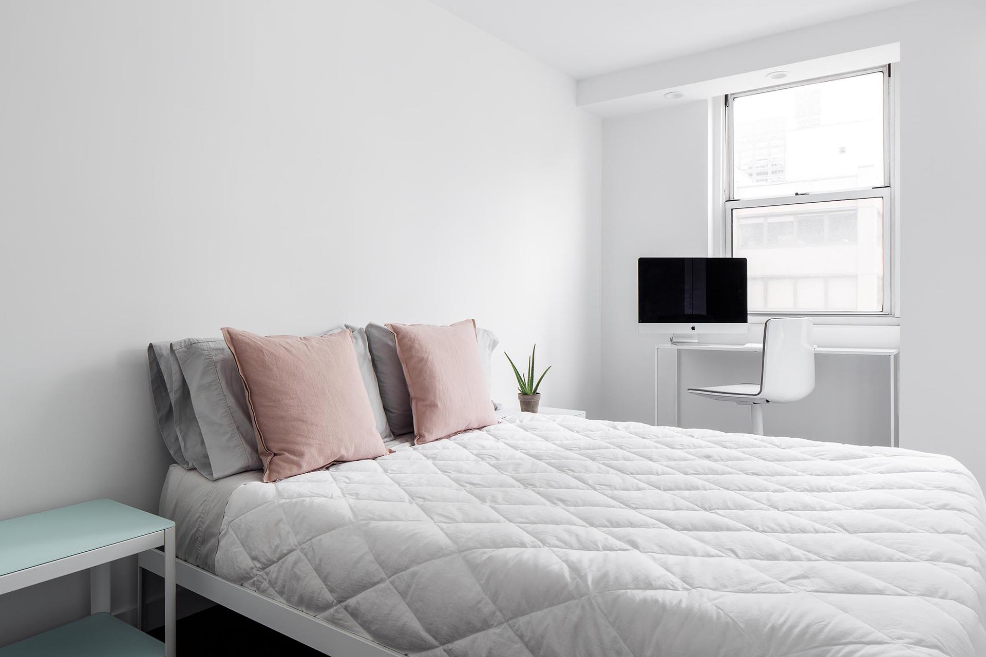 A minimally furnished bedroom with a desk by the window.