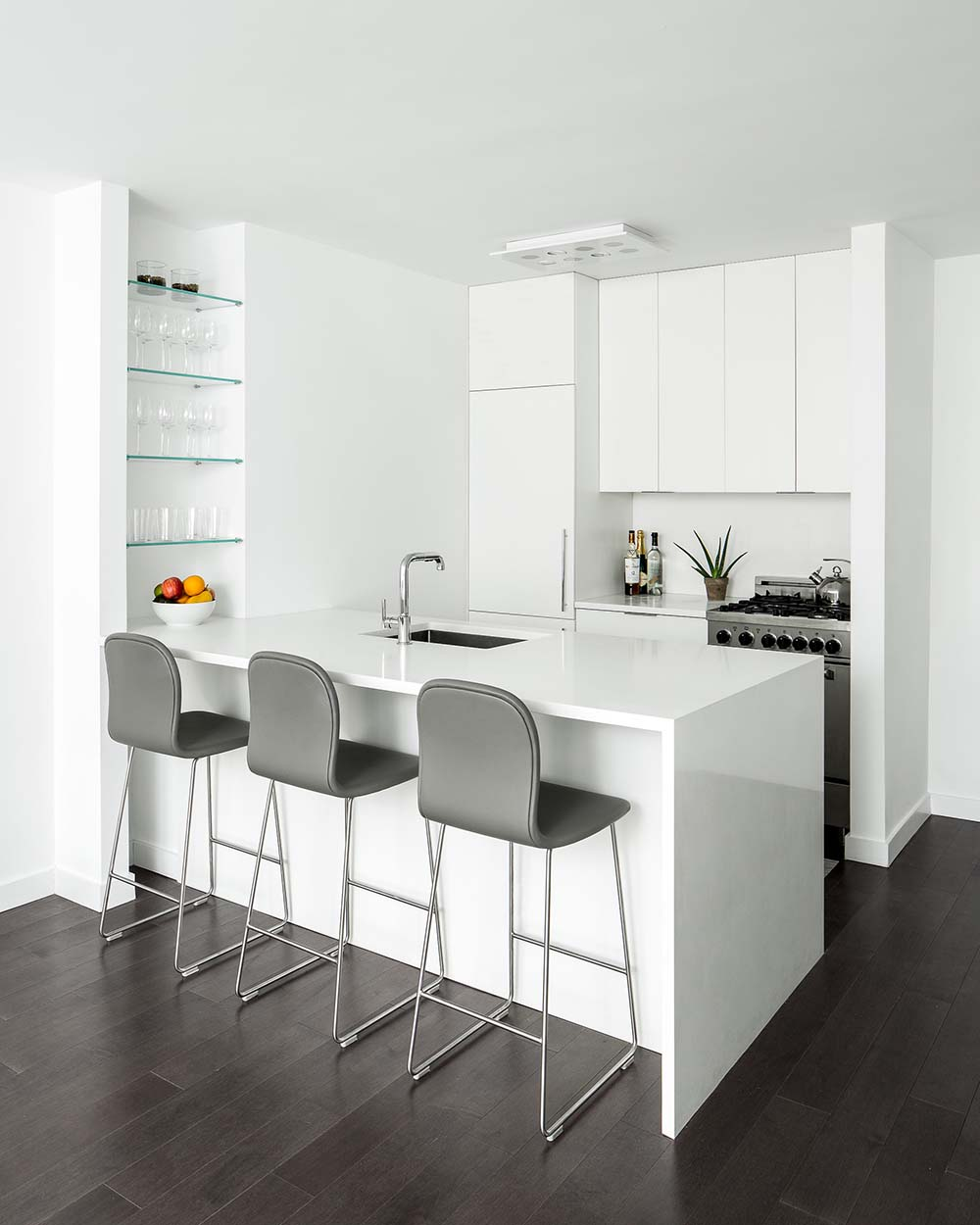 A modern white kitchen with an integrated fridge, a peninsula with a waterfall countertop, and a shelving niche with glass shelves.