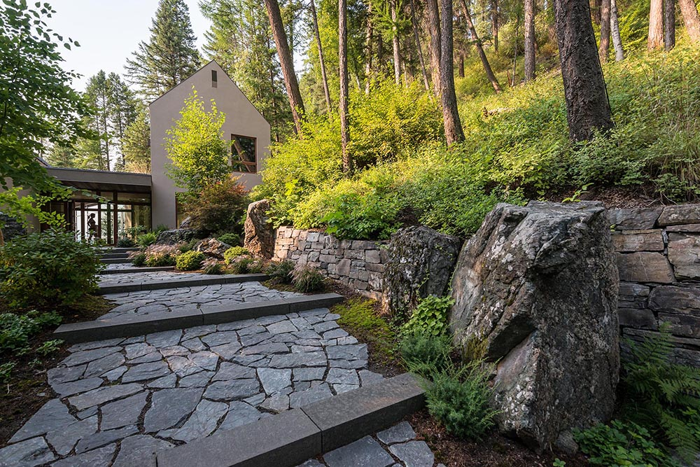 A stone pathway through the trees and shrubs leads to a small collection of stucco-clad buildings perched on a steep slope high above Whitefish Lake.