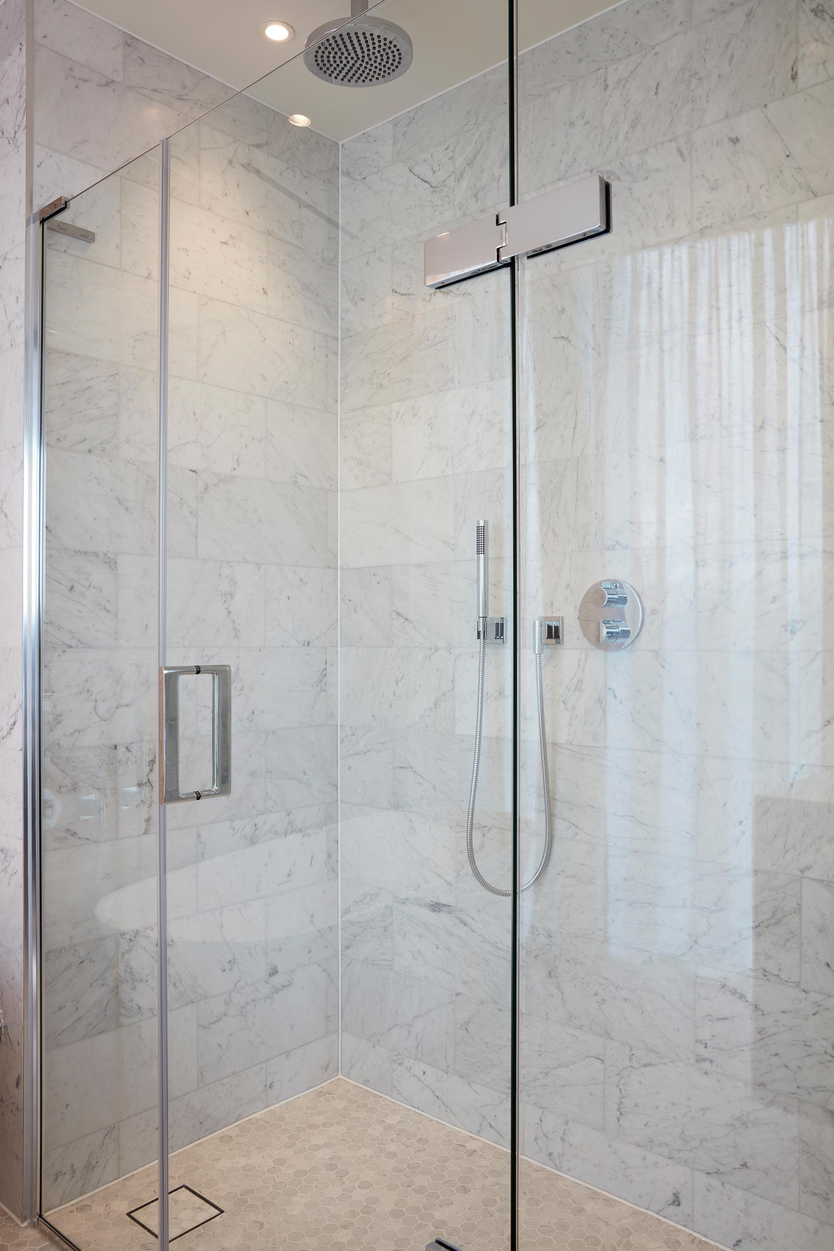 A modern walk-in shower with large gray tiles.