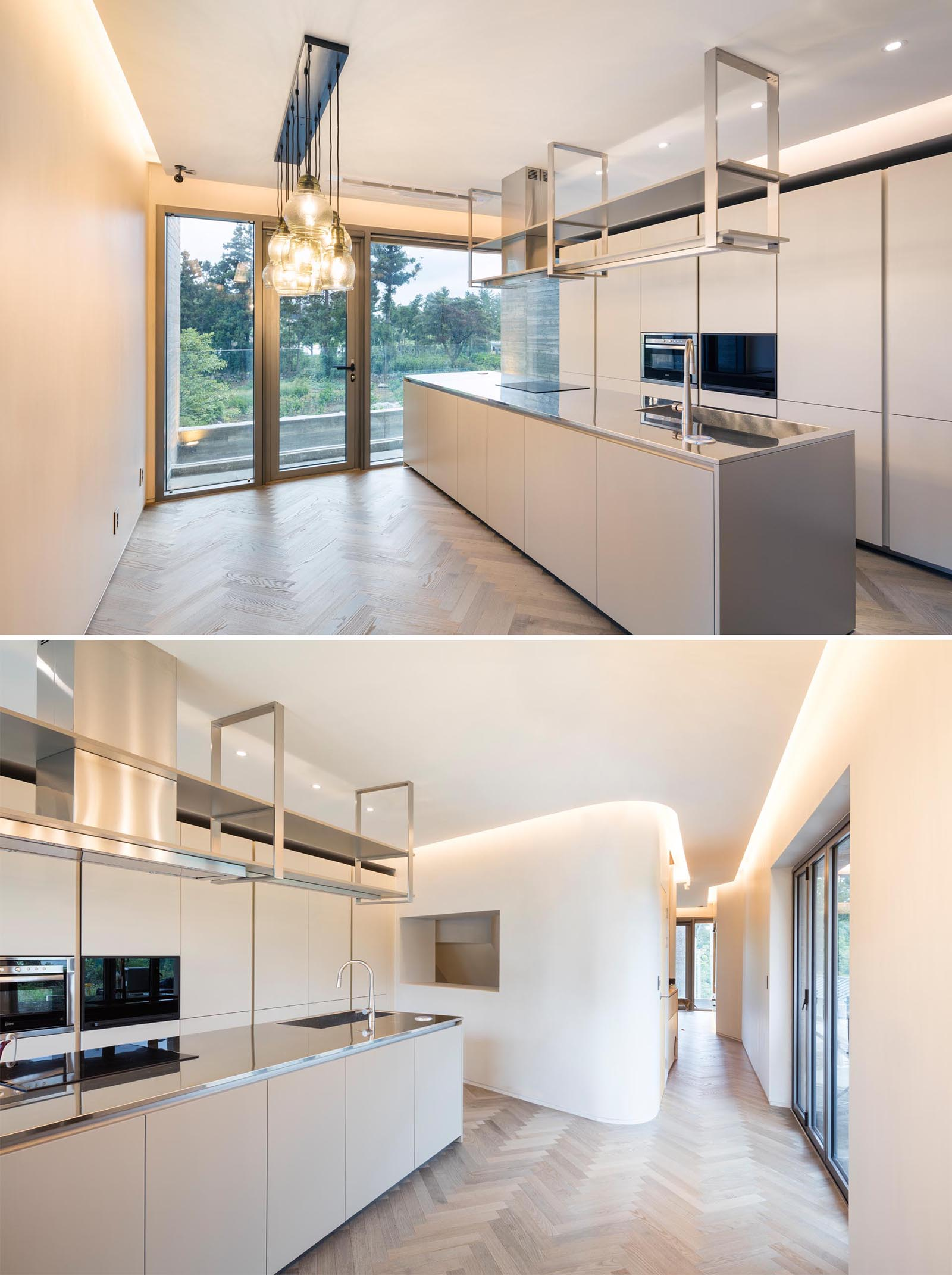 A modern kitchen with white walls and cabinets, wood flooring, and hidden lighting.