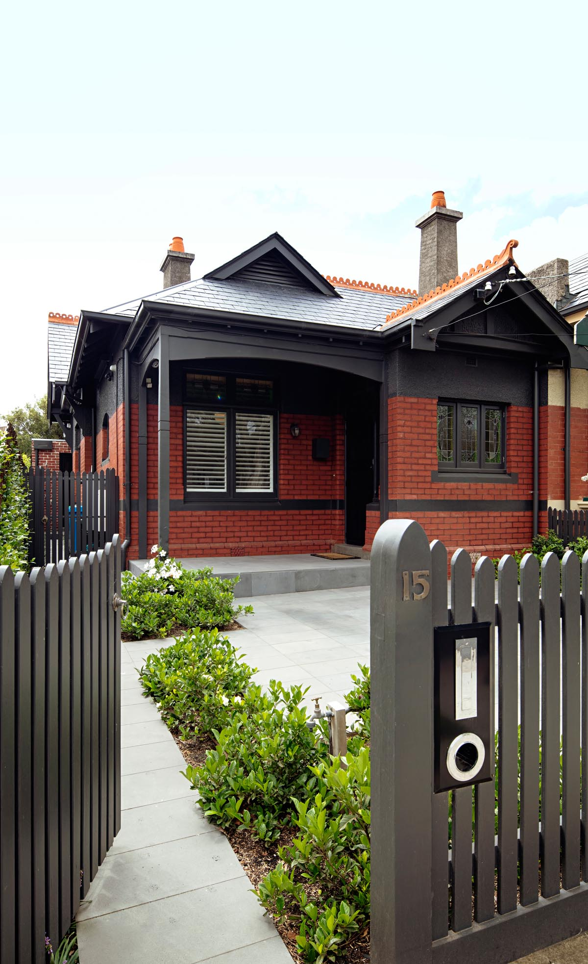 An Australian home with dark grey trim and red bricks.