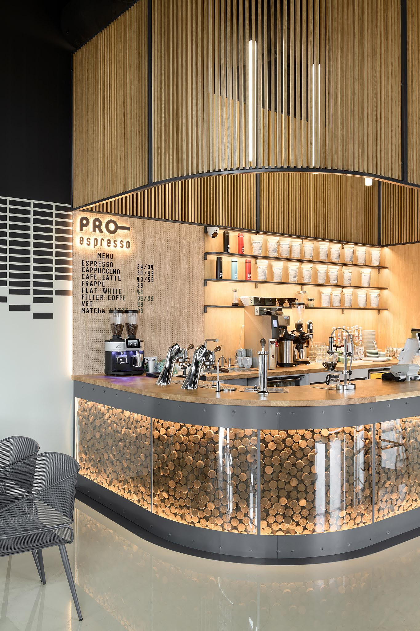 The bar counter of this modern coffee shop resembles the letter U and underneath the bar is a glass enclosed decorative accent that encloses 1300 tablets of coffee pomace.