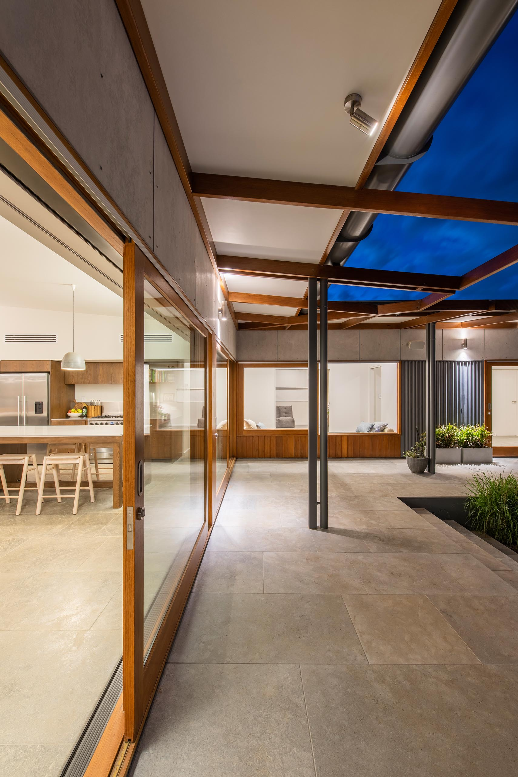 Wood-framed sliding glass doors open the living spaces to a wrap around patio.