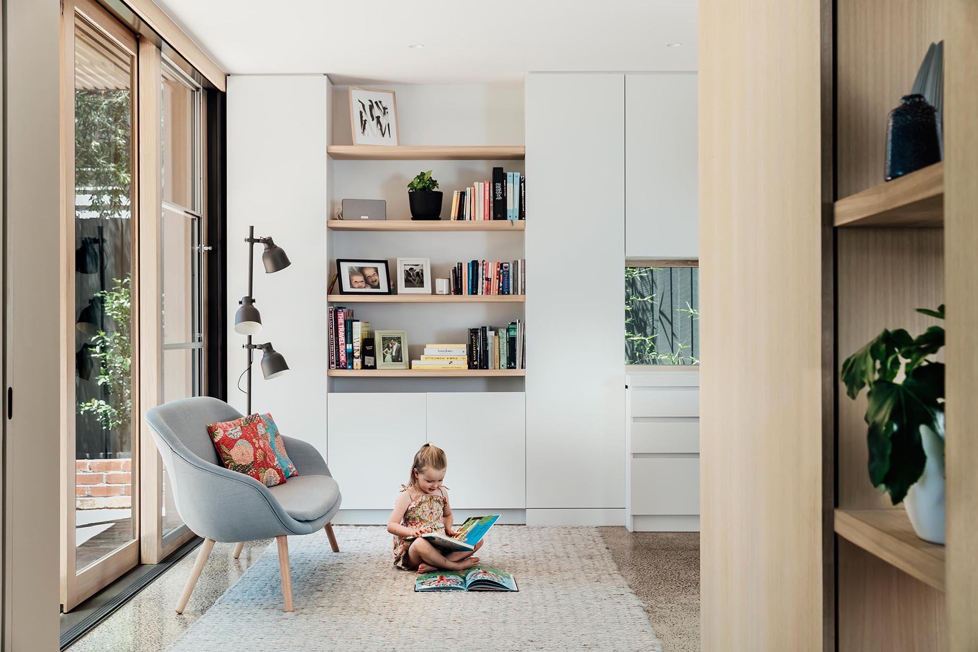 A small reading corner that's furnished with open shelving, a rug, a floor lamp, and a small sofa.