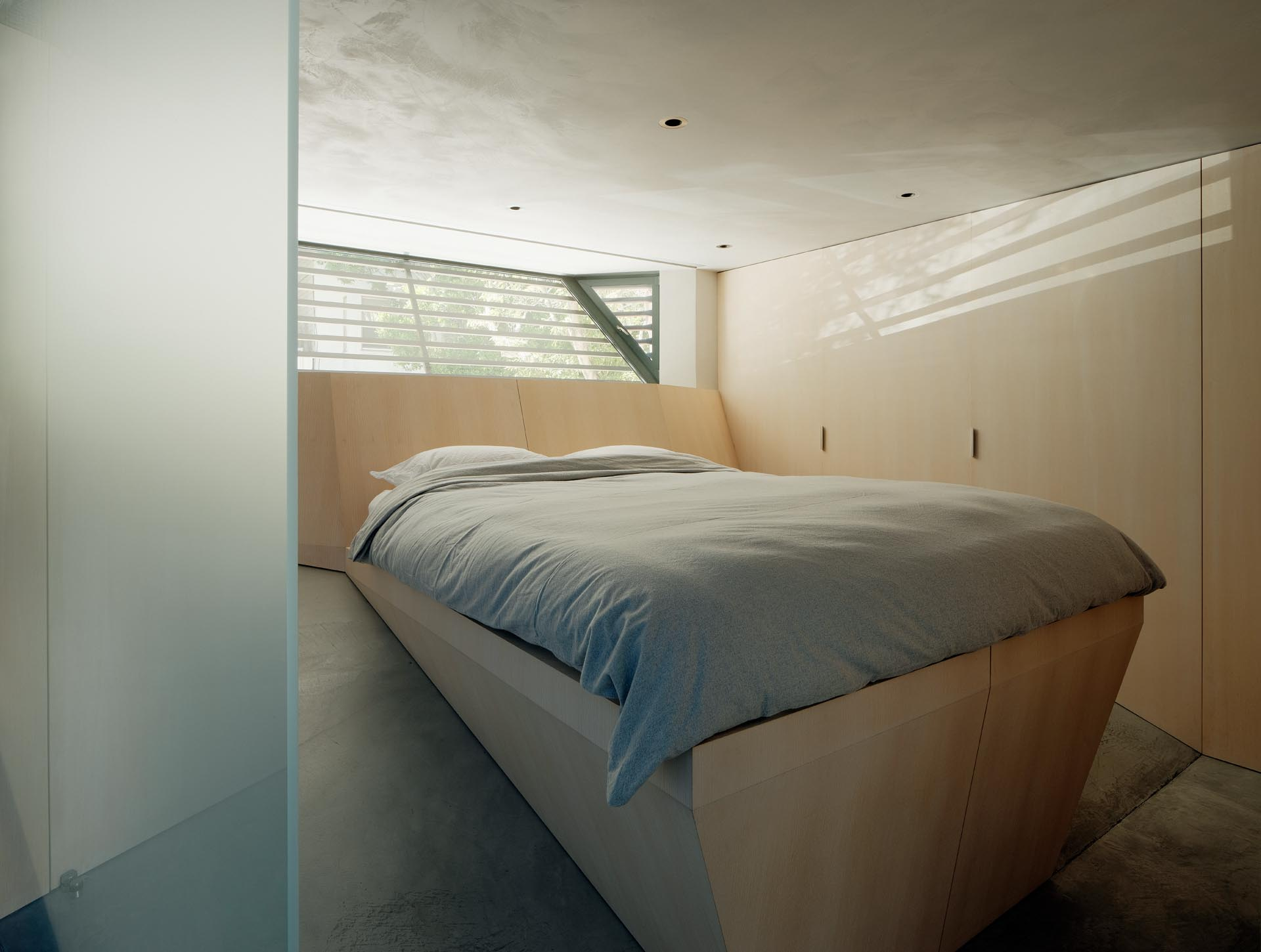 A modern bedroom with a custom designed angled wood bed frame that allows the bed to be level.