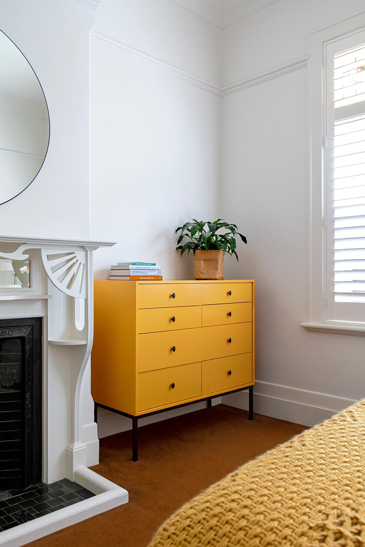 In this updated bedroom, a custom furniture piece in mustard yellow adds a colorful accent that complements both the flooring and bedspread.