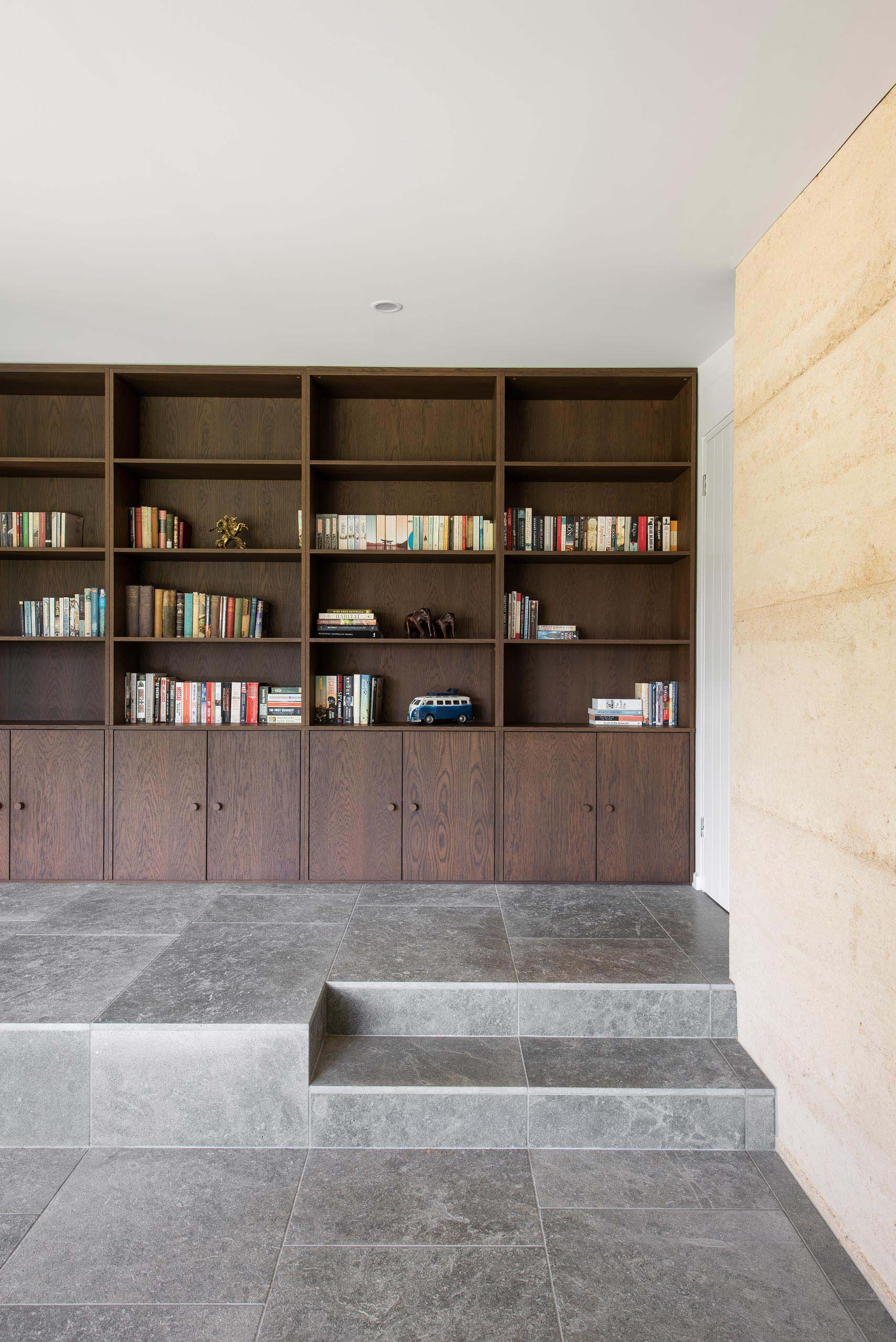 A large dark wood custom bookshelf that includes storage cabinets below.