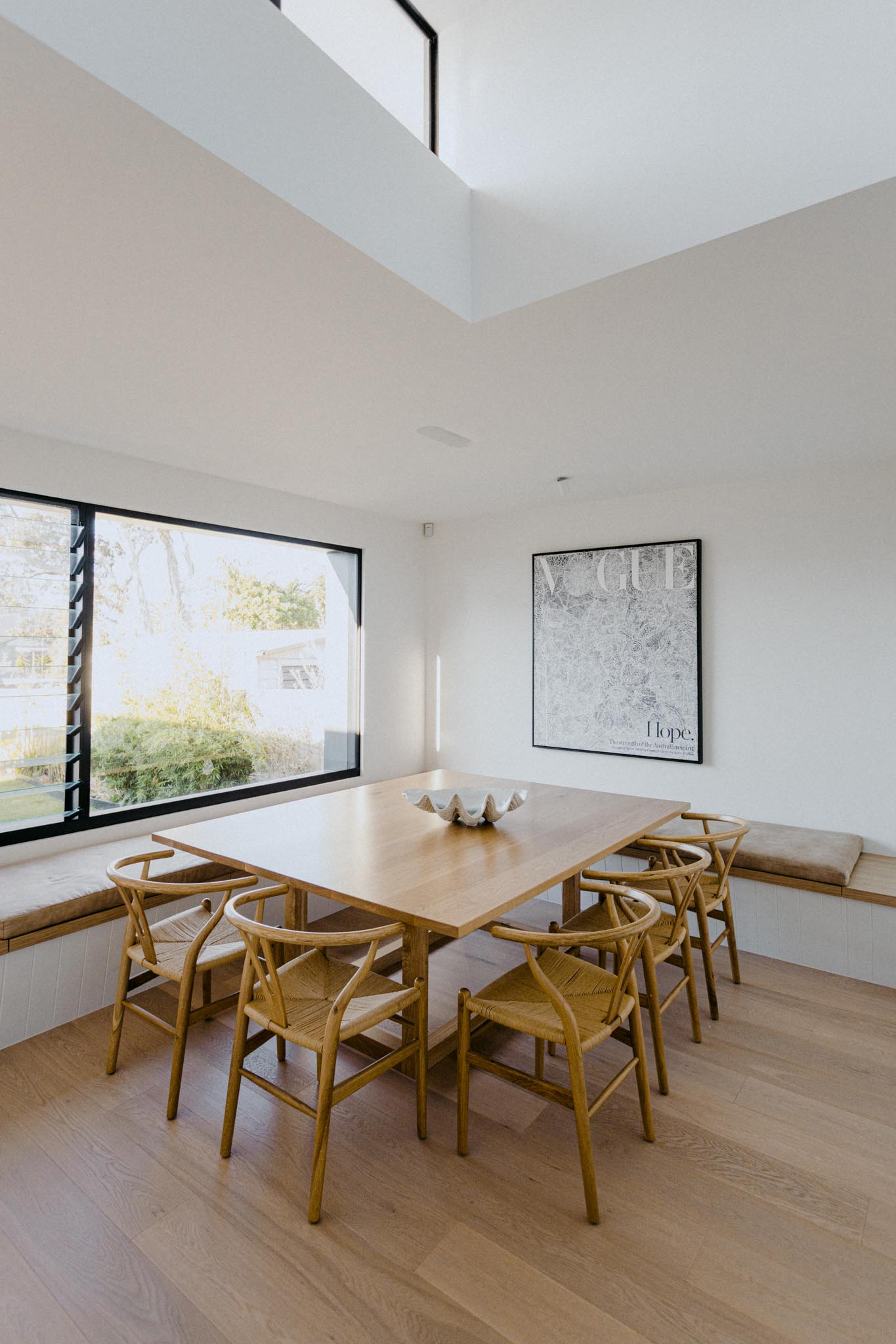 A modern dining room with benches that wrap around the corner of the room and provide plenty of seating when combined with the dining chairs.