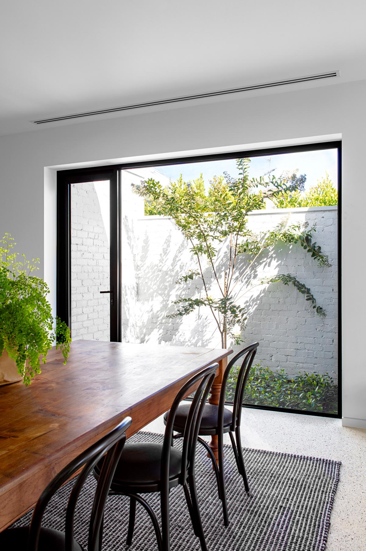 A large picture window by this dining area perfectly frames the tree outside.