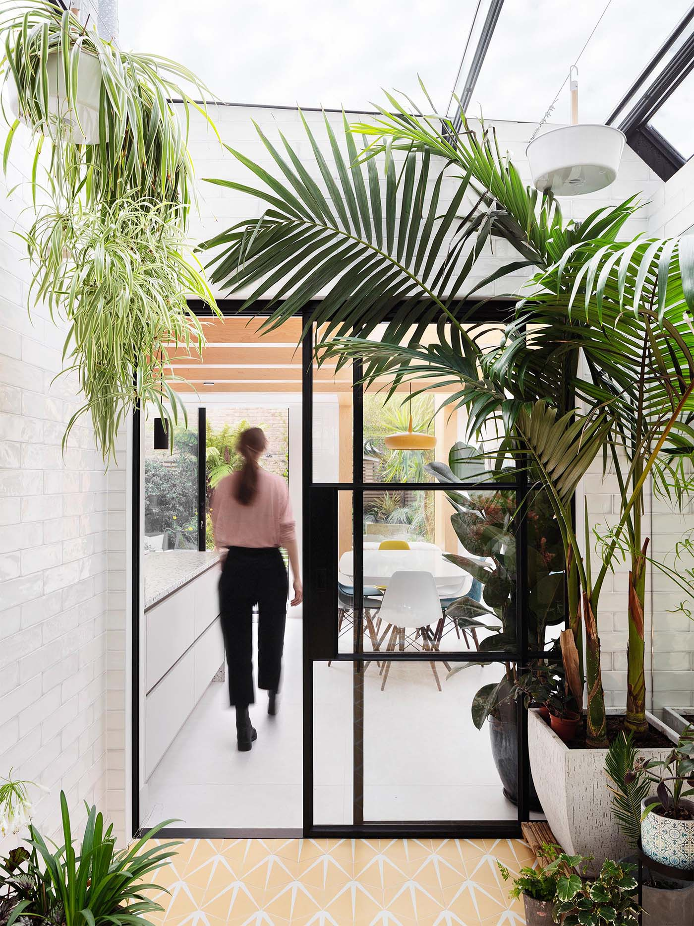 An interior garden room with automated skylights, Ochre floor tiles, an irrigation system, and plenty of plants.