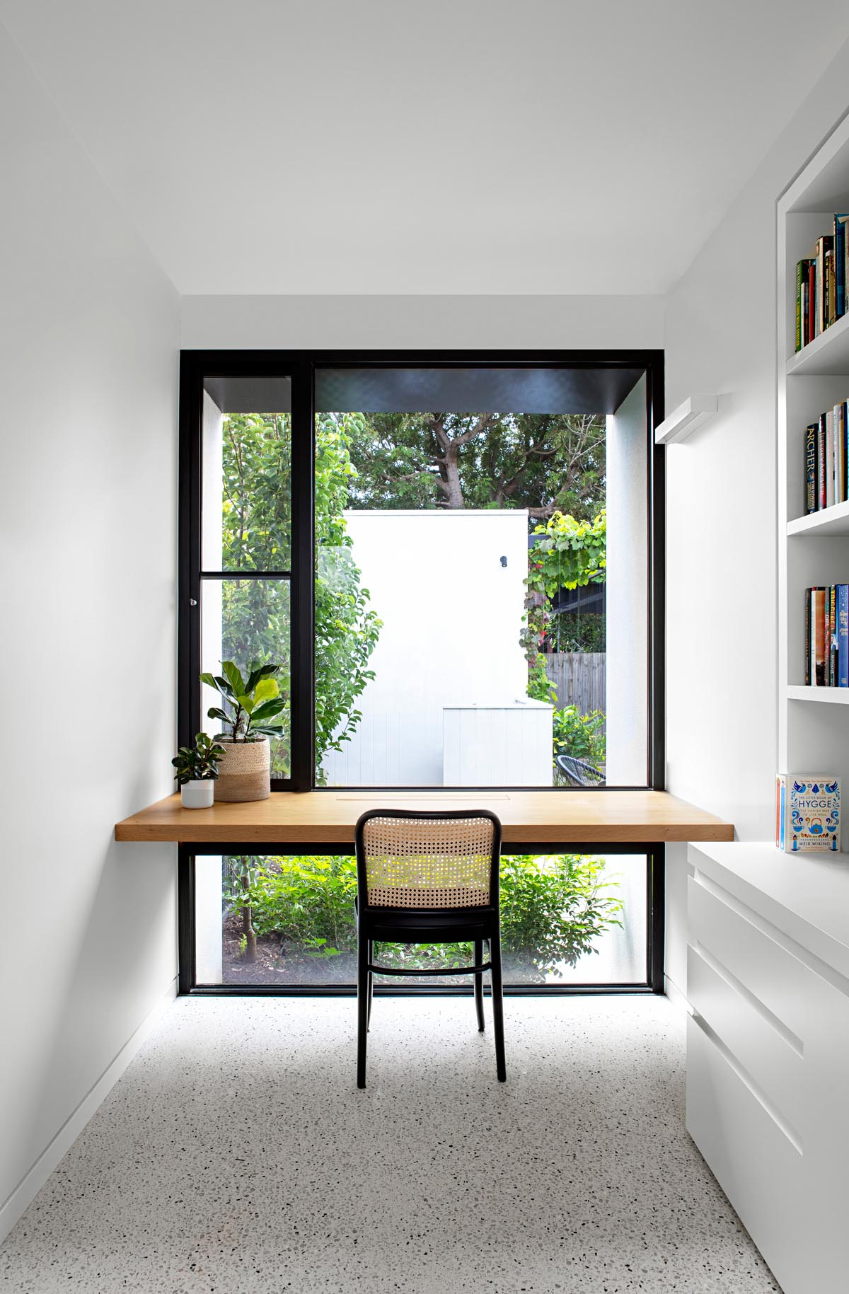 A modern home office with a solid oak wood desk that takes advantage of the window views.