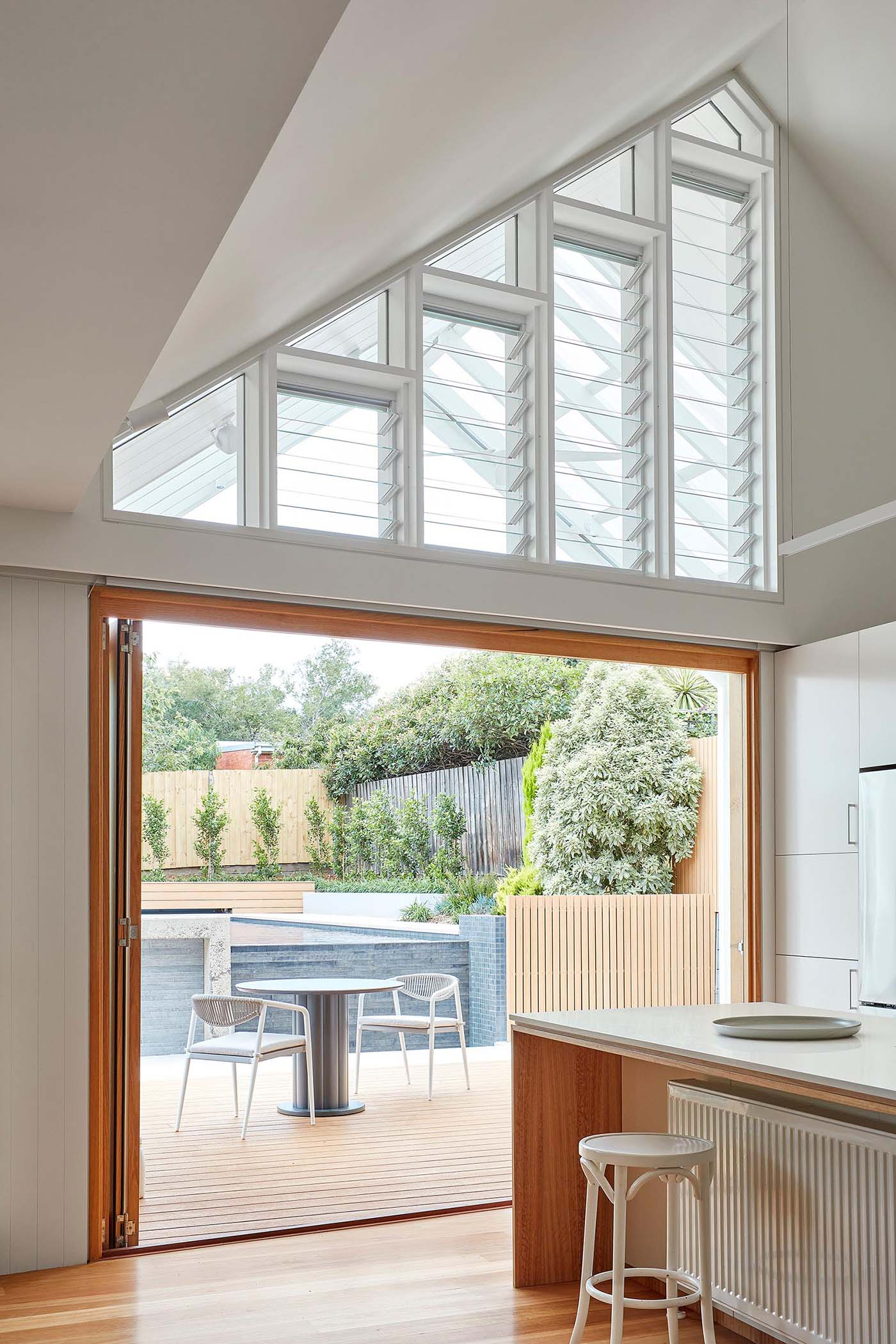 Adjacent to this modern kitchen are folding glass doors that open to a space for outdoor dining, while above, louver windows help with the air flow.