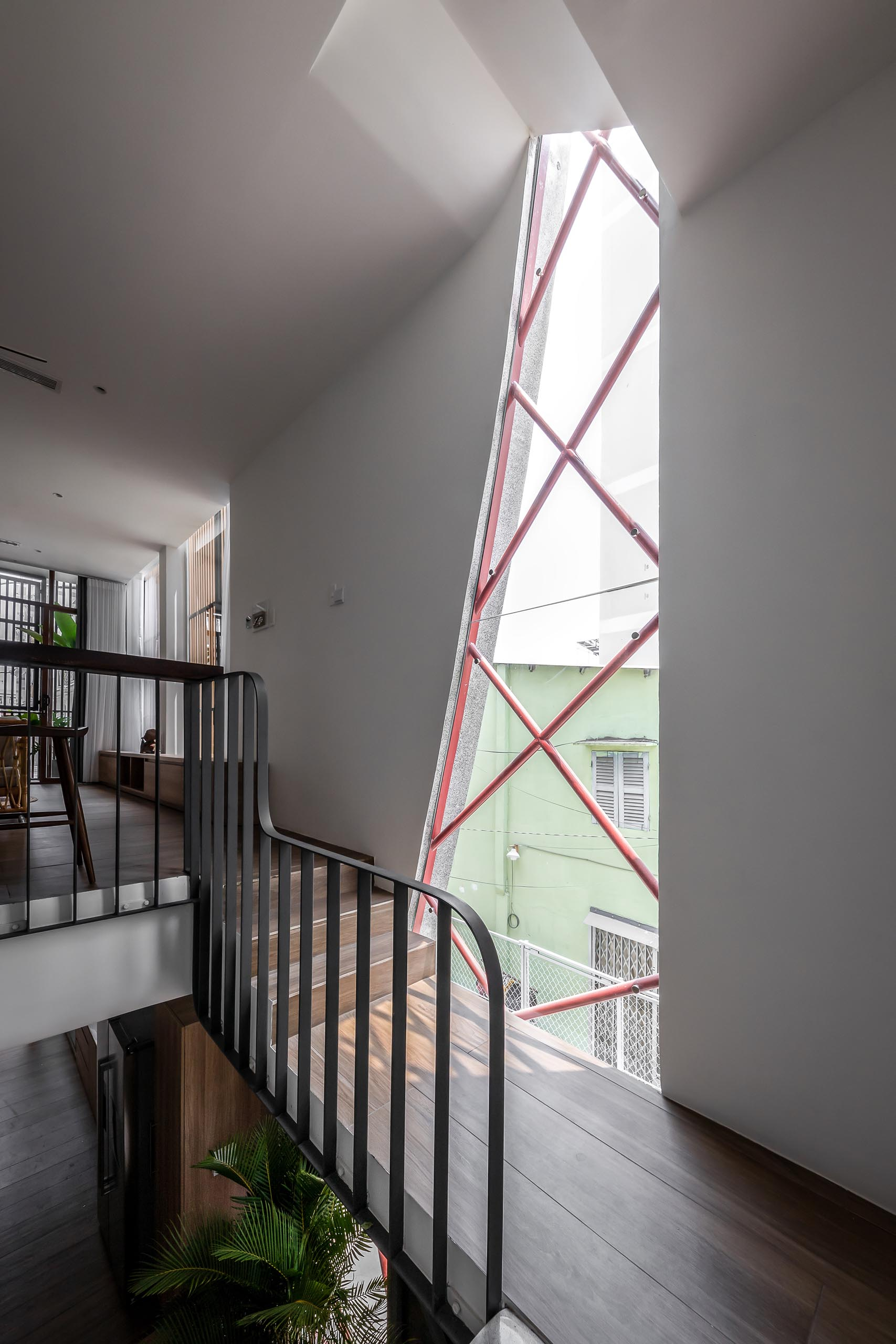 An irregular shaped window fills the entryway and staircase with natural light.
